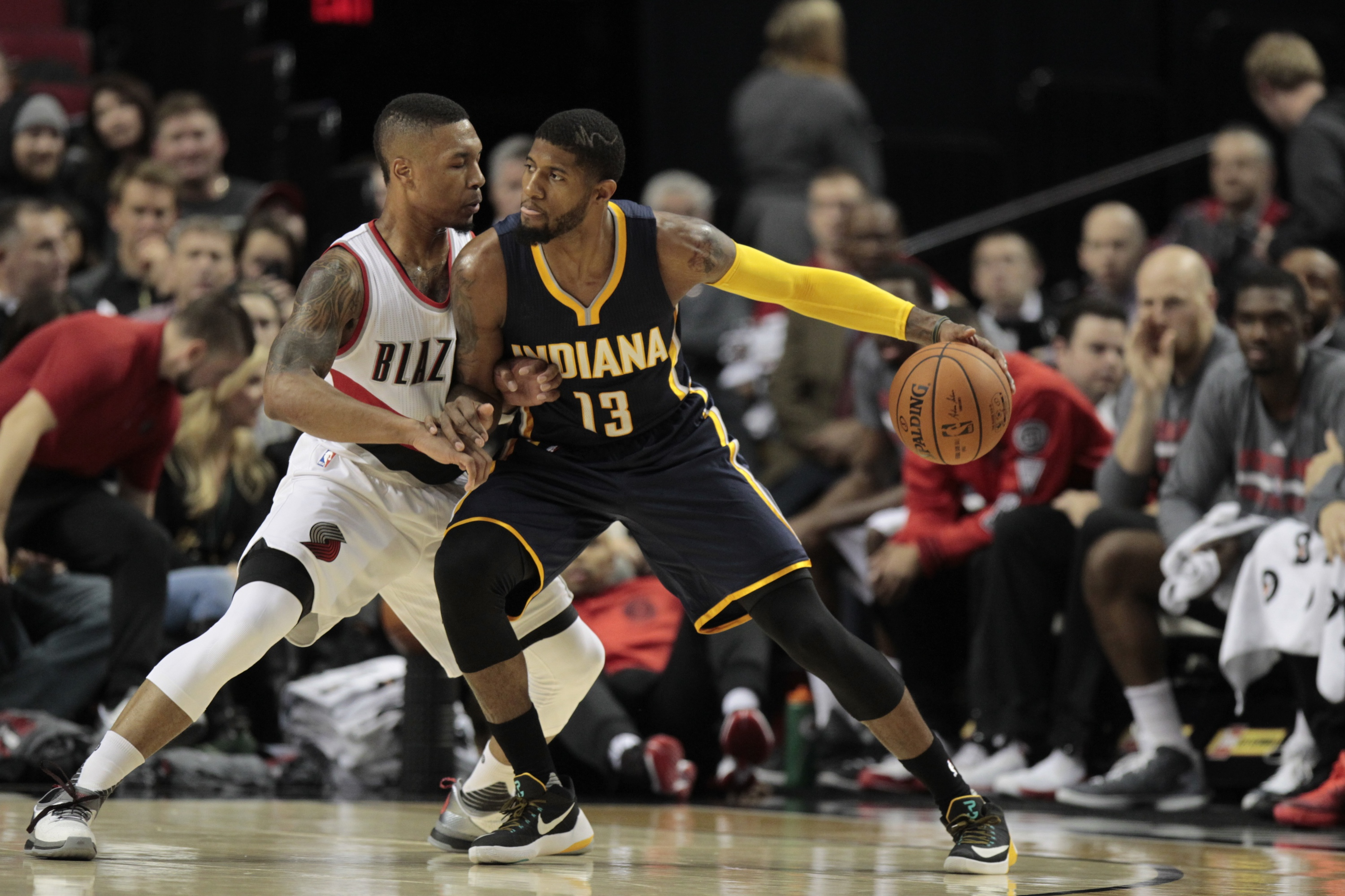 Indiana Pacers forward Paul George (13) drives against Portland Trail Blazers guard Damian Lillard during the first half of an NBA basketball game in Portland, Ore., Thursday, Dec. 3, 2015. (AP Photo/Steve Dipaola)