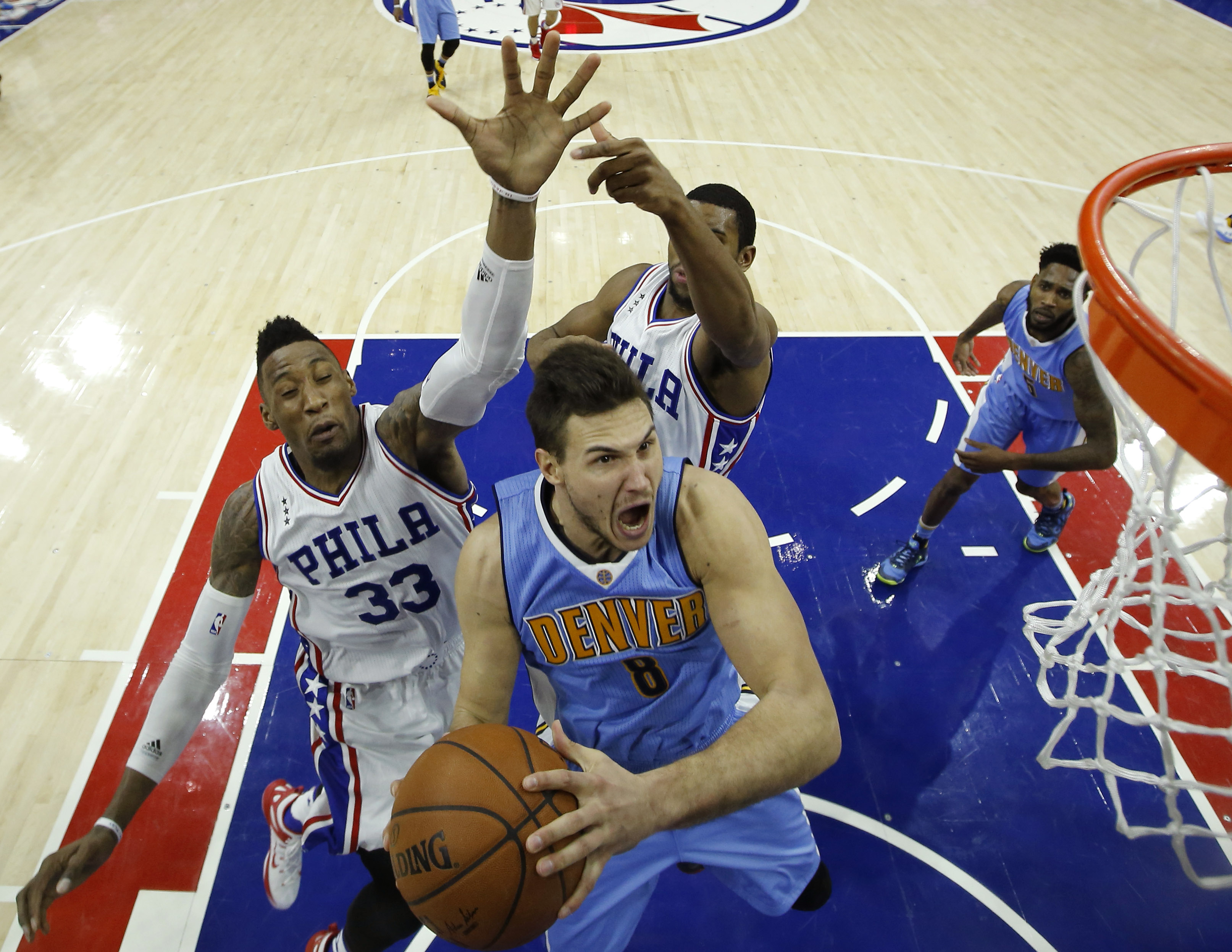 Denver Nuggets' Danilo Gallinari, center, goes up for a shot against Philadelphia 76ers' Robert Covington, left, and Hollis Thompson during the second half of an NBA basketball game, Saturday, Dec. 5, 2015, in Philadelphia. Denver won 108-15. (AP Photo/Ma