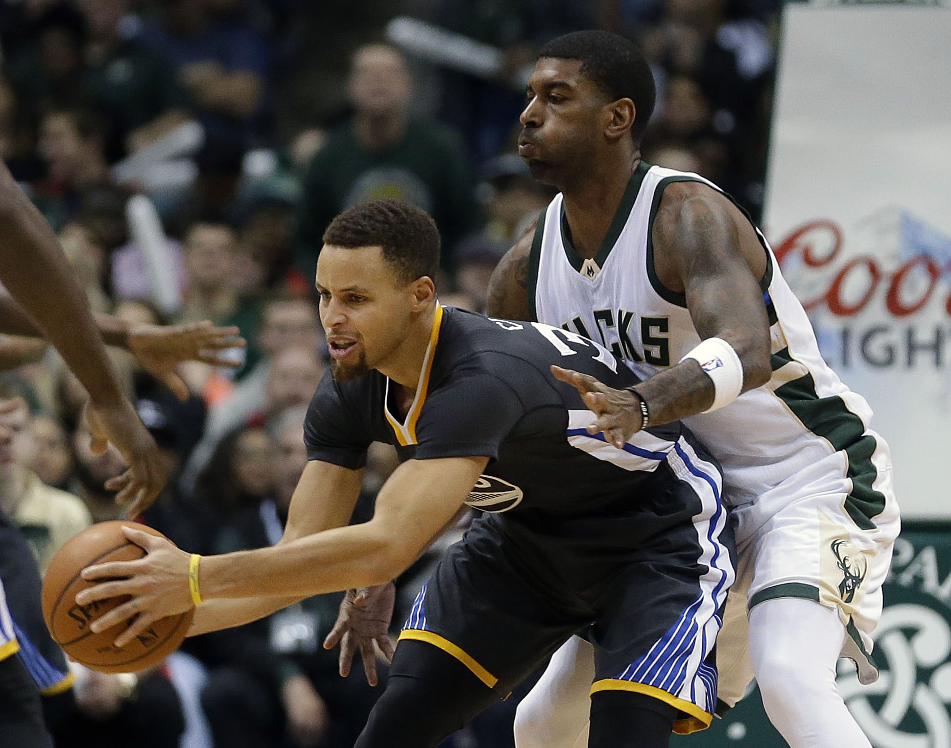 Milwaukee Bucks' O.J. Mayo defends Golden State Warriors' Stephen Curry during the second half of an NBA basketball game Saturday, Dec. 12, 2015, in Milwaukee. The Bucks won 108-95. (AP Photo/Aaron Gash)