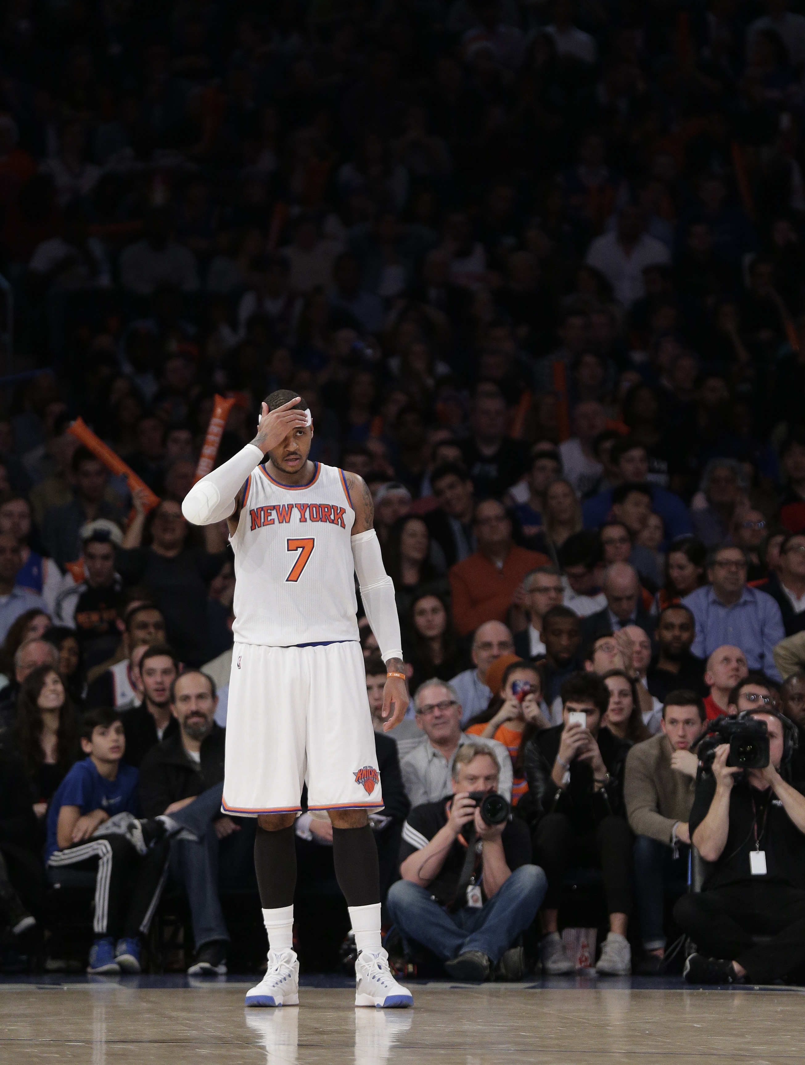New York Knicks forward Carmelo Anthony (7) adjusts his head band as he gets back on defense during the third quarter of an NBA basketball game against the Orlando Magic, Monday, Dec. 21, 2015, in New York. The Magic won 107-99. (AP Photo/Julie Jacobson)