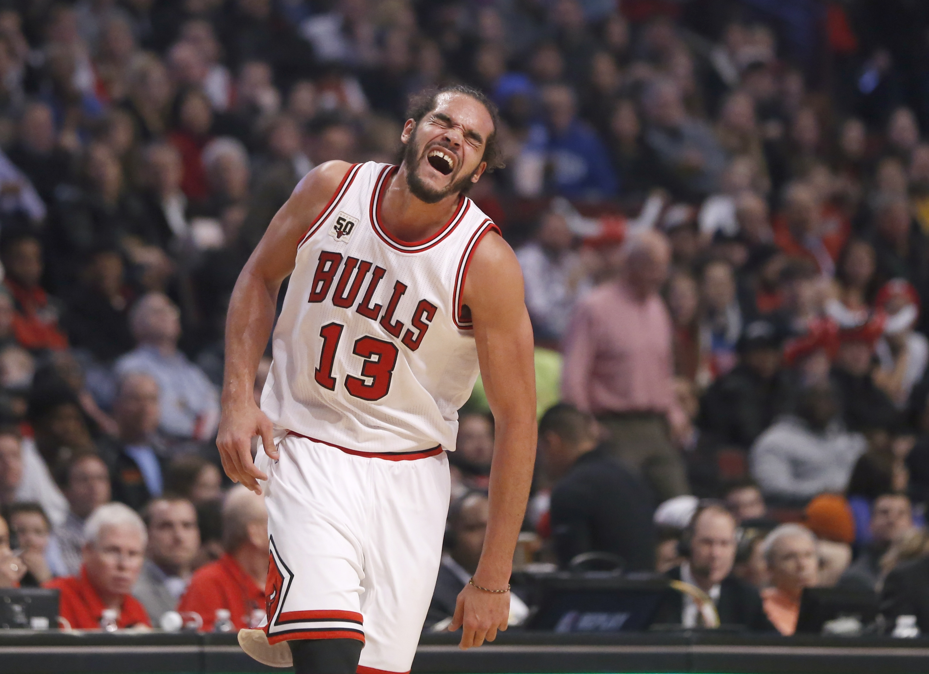 Chicago Bulls center Joakim Noah runs down the court with an apparent injury to his left shoulder during the second half of an NBA basketball game against the Brooklyn Nets on Monday, Dec. 21, 2015, in Chicago. The Nets won 105-102. (AP Photo/Charles Rex