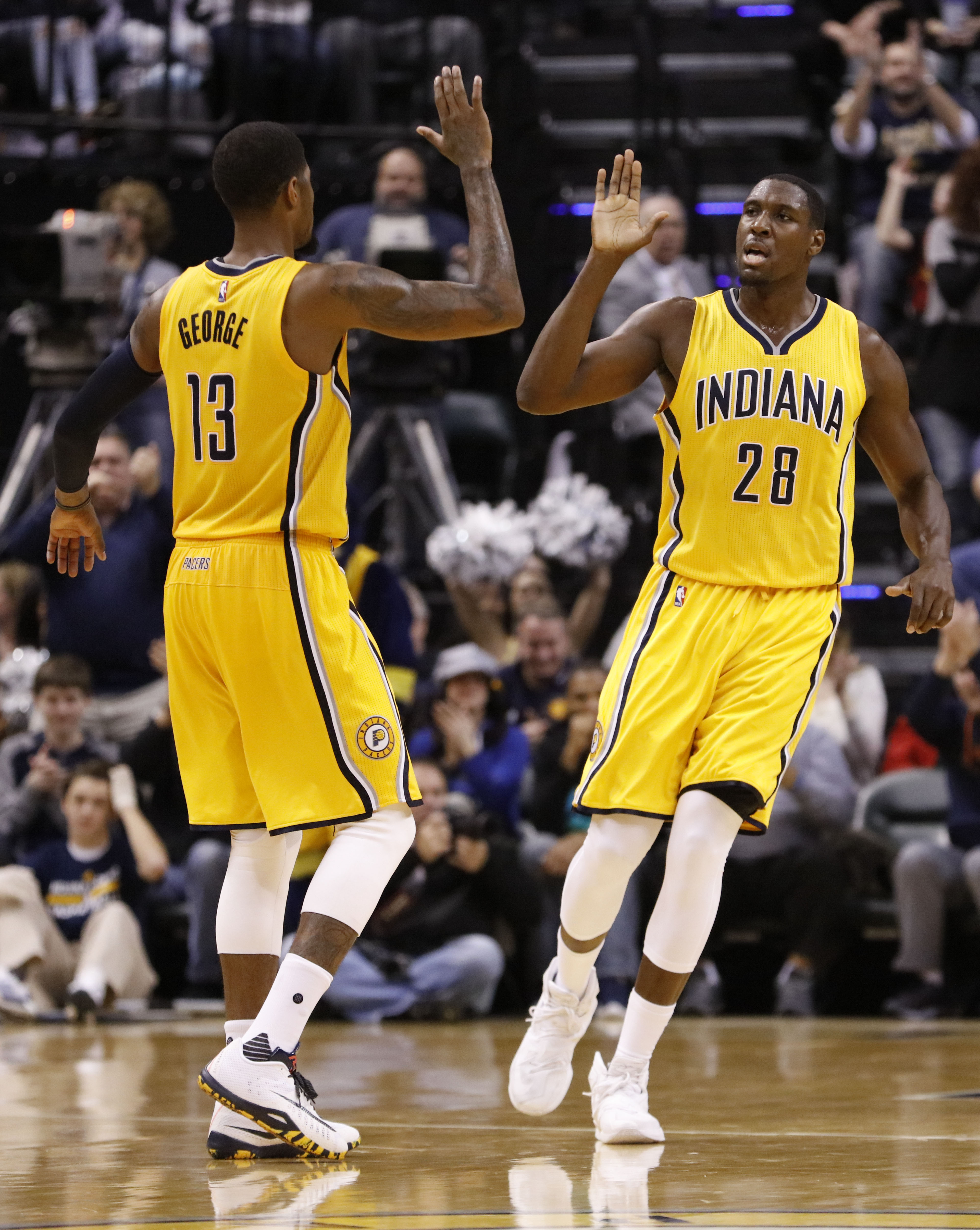Indiana Pacers center Ian Mahinmi (28) celebrates a late basket off an offensive rebound with teammate Paul George (13) during the second half of an NBA basketball game against the Atlanta Hawks in Indianapolis, Monday, Dec. 28, 2015. The Pacers won 93-87