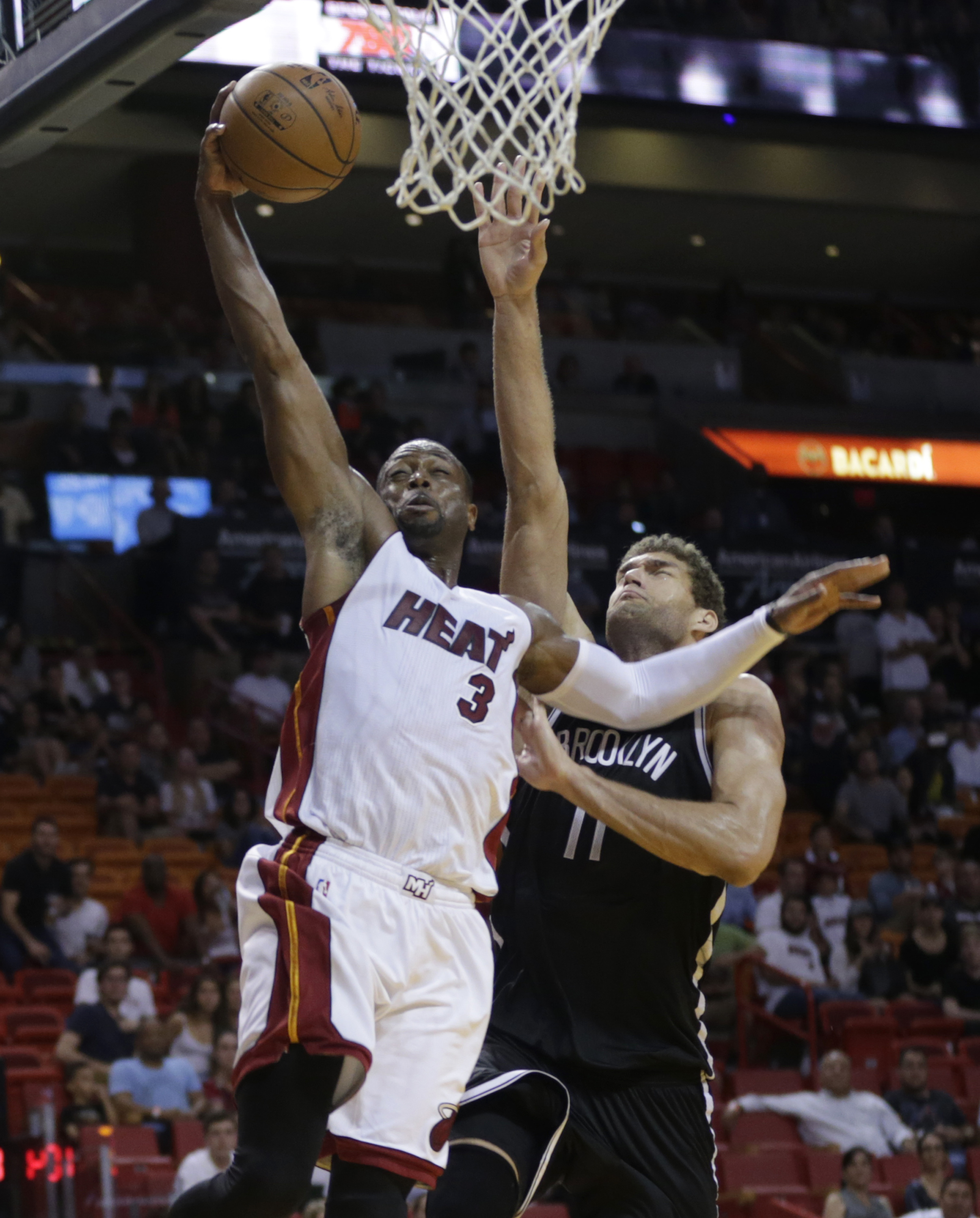 Miami Heat's Dwyane Wade (3) drives to the basket as Brooklyn Nets' Brook Lopez (11) defends during the second half of an NBA basketball game, Monday, Dec. 28, 2015, in Miami. The Nets defeated the Heat 111-105. (AP Photo/Lynne Sladky)