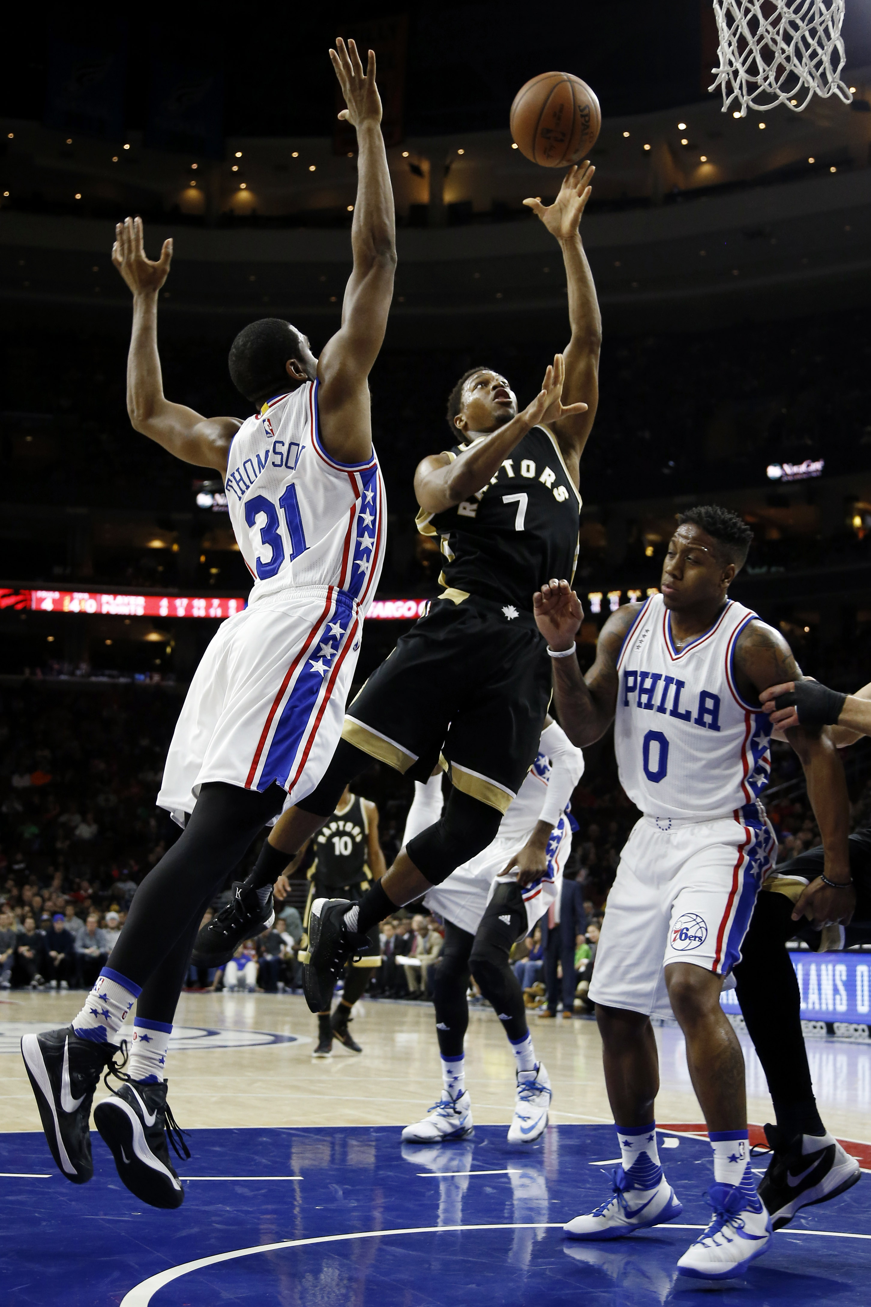 Toronto Raptors' Kyle Lowry (7) goes up for a shot between Philadelphia 76ers' Hollis Thompson (31) and Isaiah Canaan (0) during the first half of an NBA basketball game, Saturday, Jan. 9, 2016, in Philadelphia. (AP Photo/Matt Slocum)