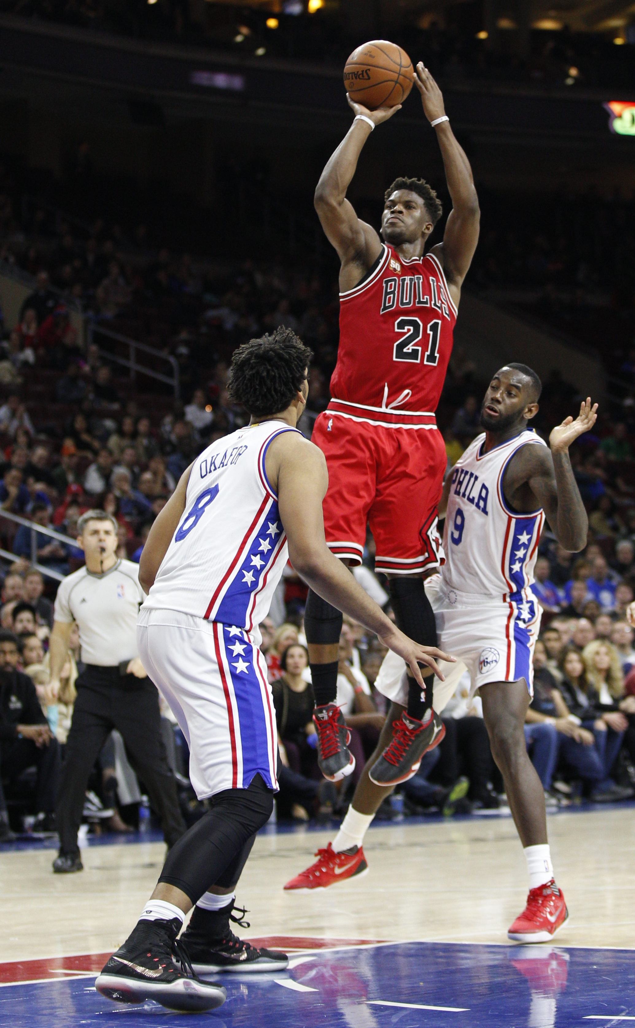 Chicago Bulls' Jimmy Butler is fouled by Philadelphia 76ers' JaKarr Sampson, right, as 76ers' Jahlil Okafor helps defend during the second half of an NBA basketball game Thursday, Jan. 14, 2016, in Philadelphia. The Bulls won 115-111 in overtime. (AP Phot