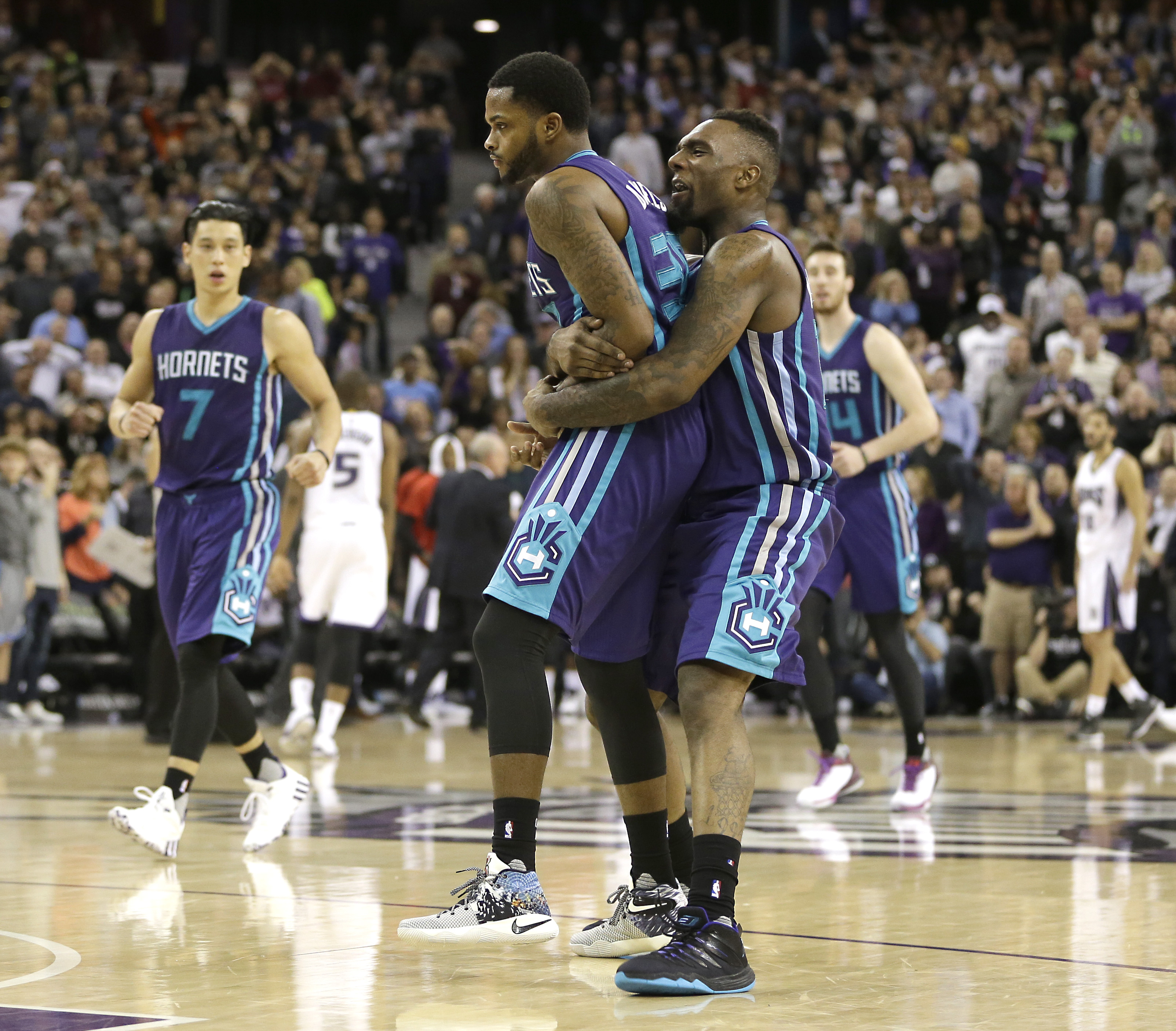 Charlotte Hornets guard Troy Daniels, left, is carried off the court by  Hornets forward P.J. Hairston, right, after Daniels made a 3-point shot to give the Hornets a 129-128 double overtime win over the Sacramento Kings in an NBA basketball game Monday,