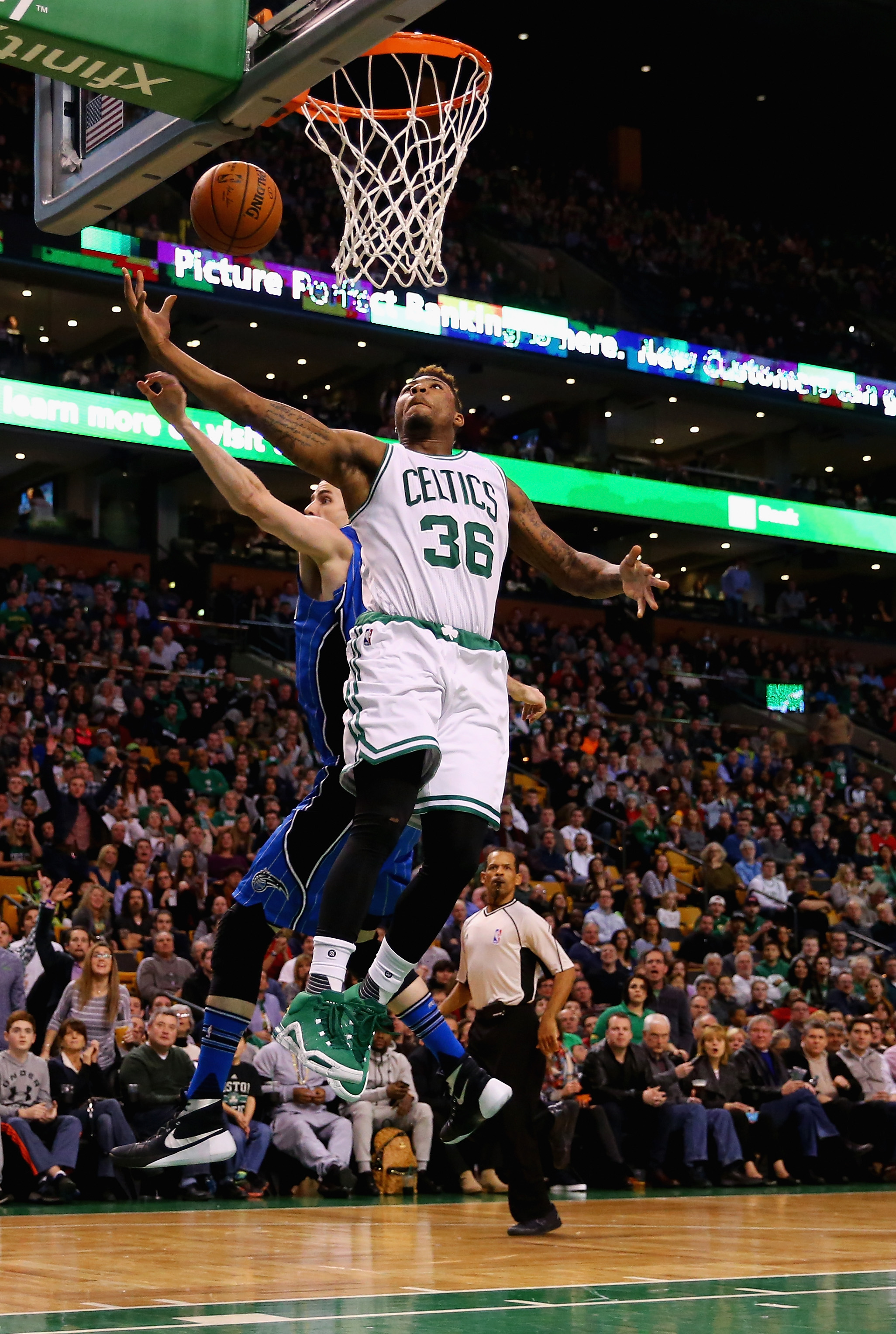 BOSTON, MA - JANUARY 29:  Marcus Smart #36 of the Boston Celtics hits a shot with pressure from Jason Smith #14 of the Orlando Magic during the third quarter at TD Garden on January 29, 2016 in Boston, Massachusetts. (Photo by Maddie Meyer/Getty Images)