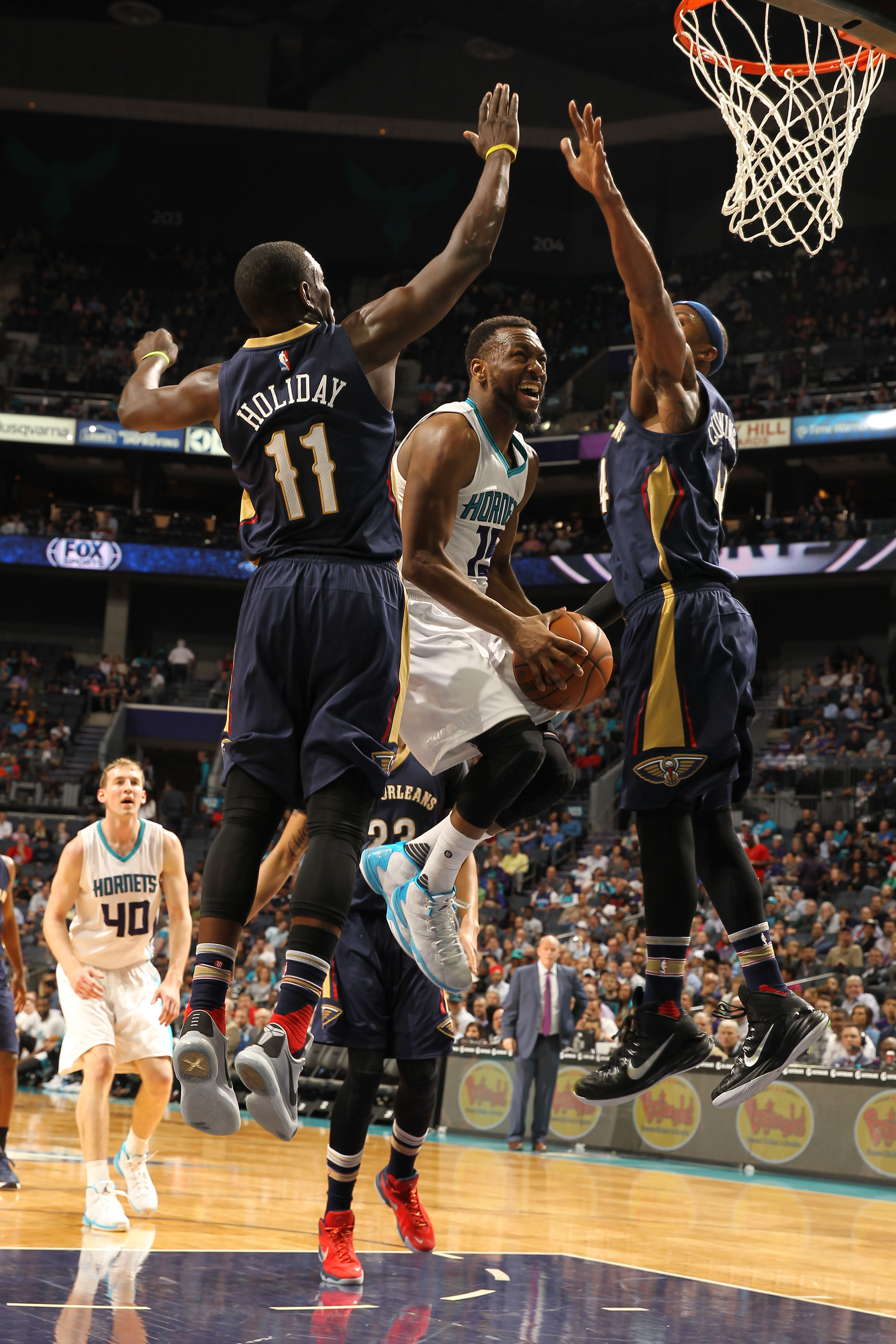 CHARLOTTE, NC - MARCH 09:  Kemba Walker #15 of the Charlotte Hornets shoots against Jrue Holiday #11 and Dante Cunningham #44 of the New Orleans Pelicans during the game at the Time Warner Cable Arena on March 09, 2016 in Charlotte, North Carolina. (Photo