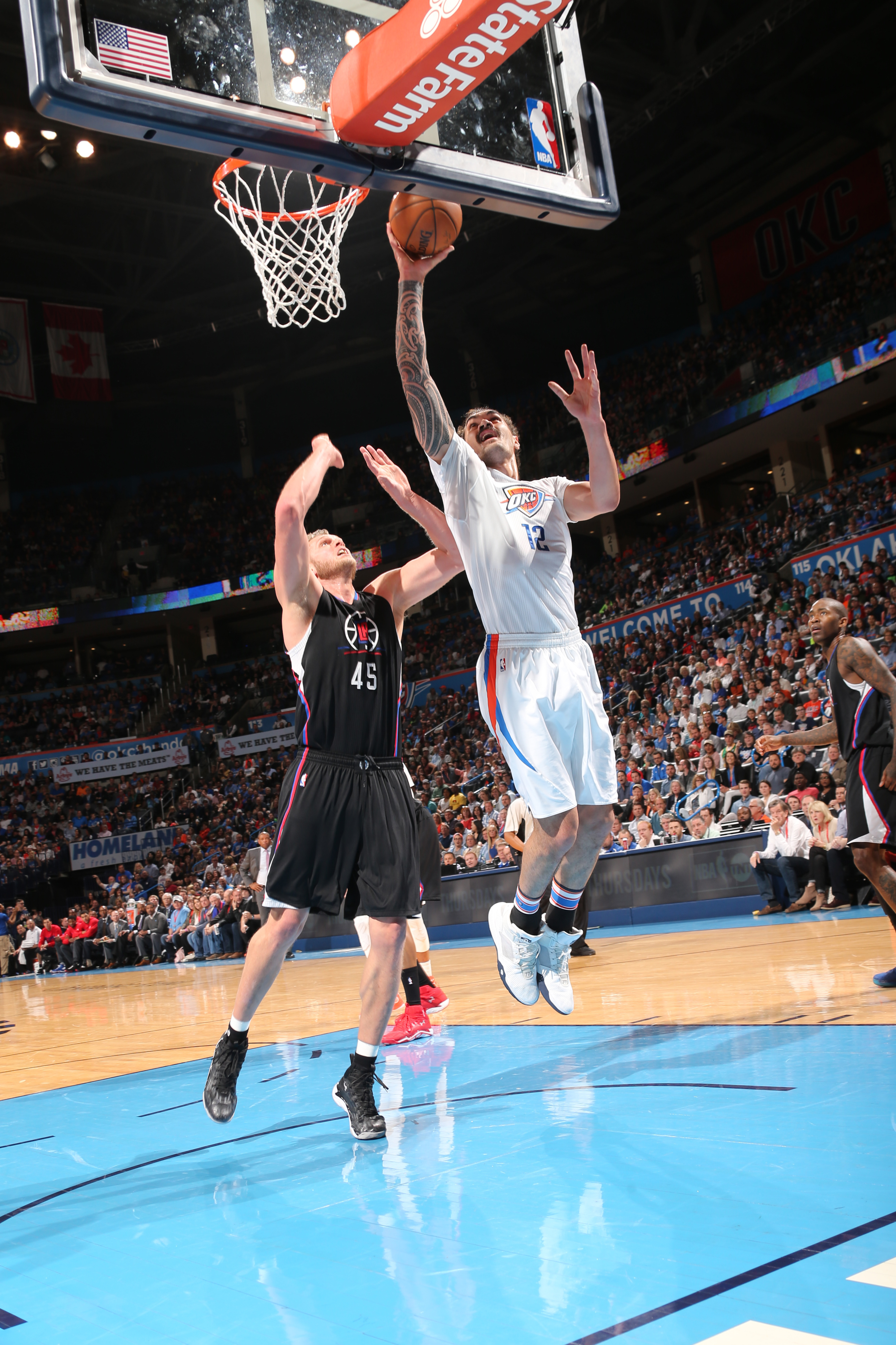 OKLAHOMA CITY, OK - MARCH 31:  Steven Adams #12 of the Oklahoma City Thunder goes to the basket against Cole Aldrich #45 of the Los Angeles Clippers on March 31, 2016 at Chesapeake Energy Arena in Oklahoma City, Oklahoma. (Photo by Layne Murdoch/NBAE via
