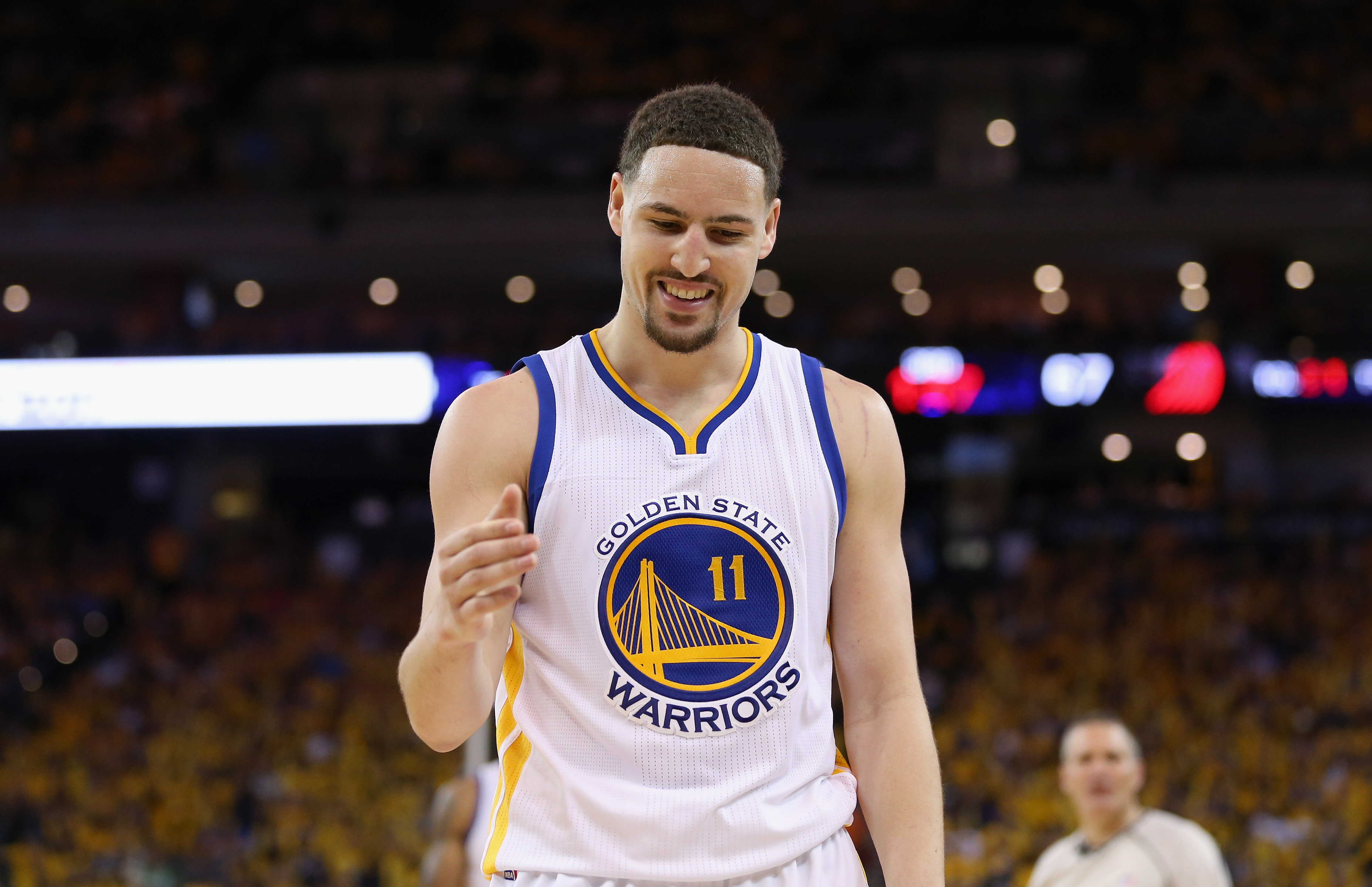 OAKLAND, CA - MAY 01:  Klay Thompson #11 of the Golden State Warriors smiles as he goes to help Leandro Barbosa #19 off the ground during their game against the Portland Trail Blazers during Game One of the Western Conference Semifinals for the 2016 NBA P