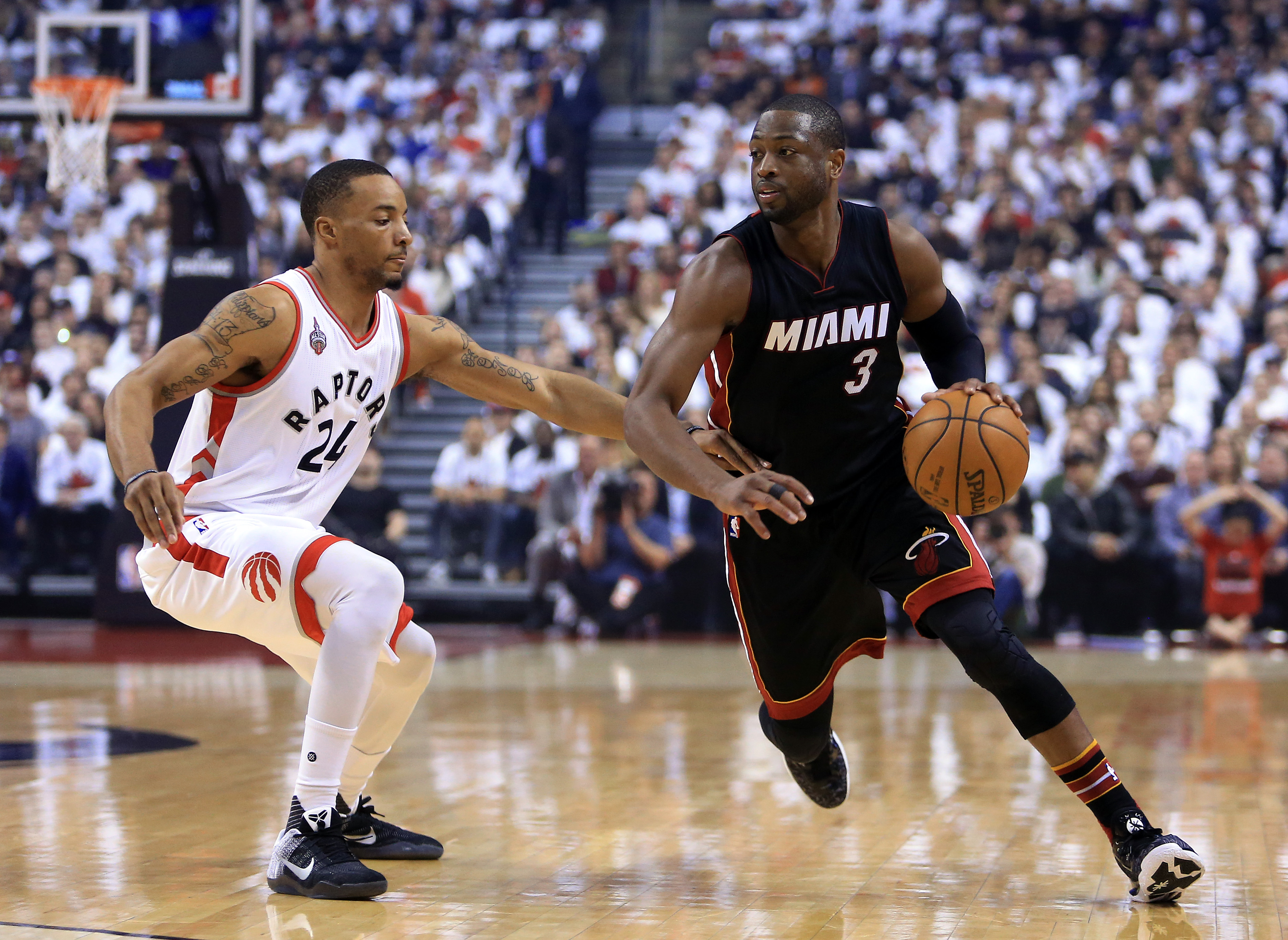 TORONTO, ON - MAY 03:  Dwyane Wade #3 of the Miami Heat dribbles the ball as Norman Powell #24 of the Toronto Raptors defends in the first half of Game One of the Eastern Conference Semifinals during the 2016 NBA Playoffs at the Air Canada Centre on May 3