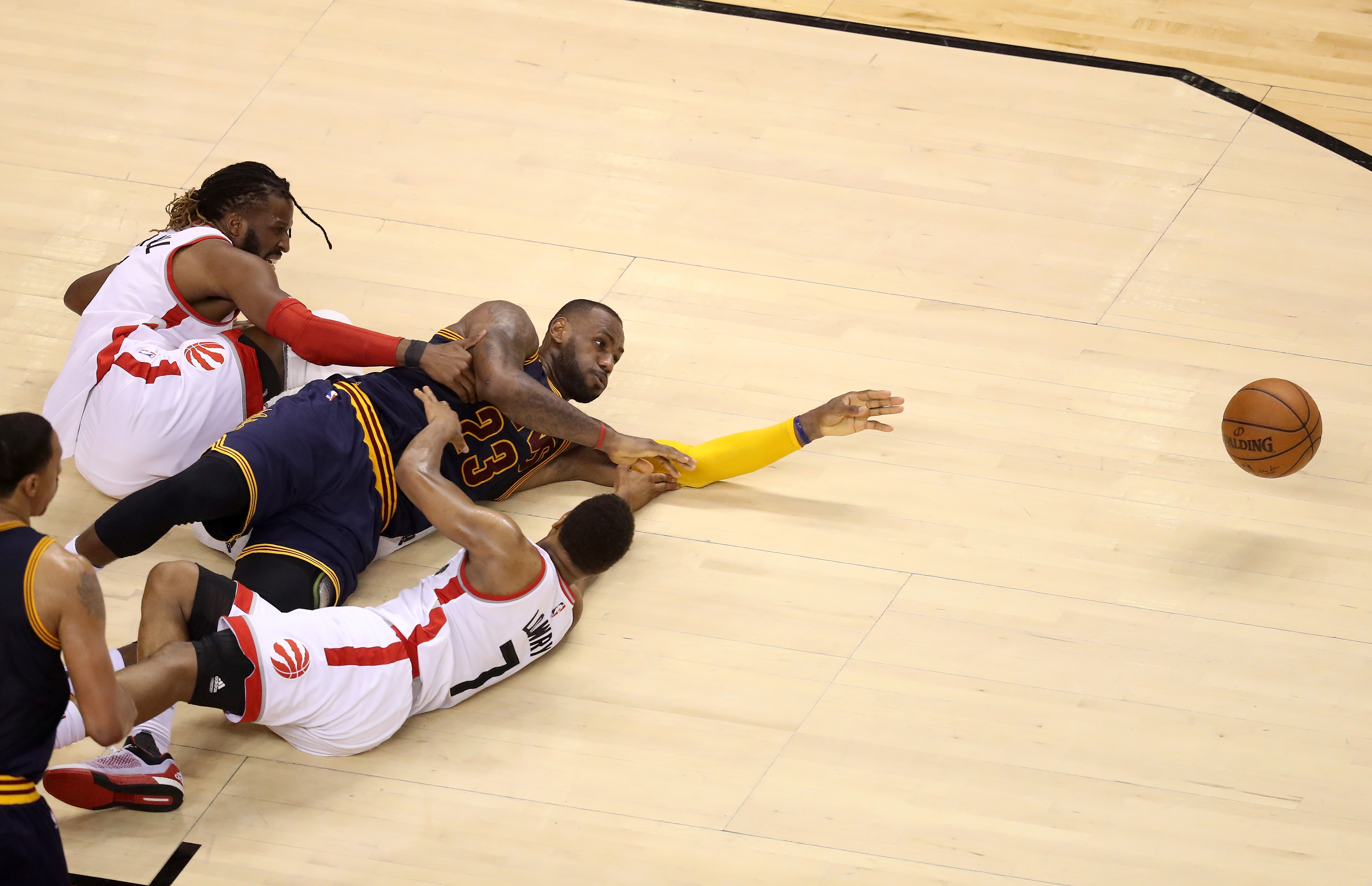 TORONTO, ON - MAY 23:  LeBron James #23 of the Cleveland Cavaliers competes for a loose ball late in the game against DeMarre Carroll #5 and Kyle Lowry #7 of the Toronto Raptors in game four of the Eastern Conference Finals during the 2016 NBA Playoffs at