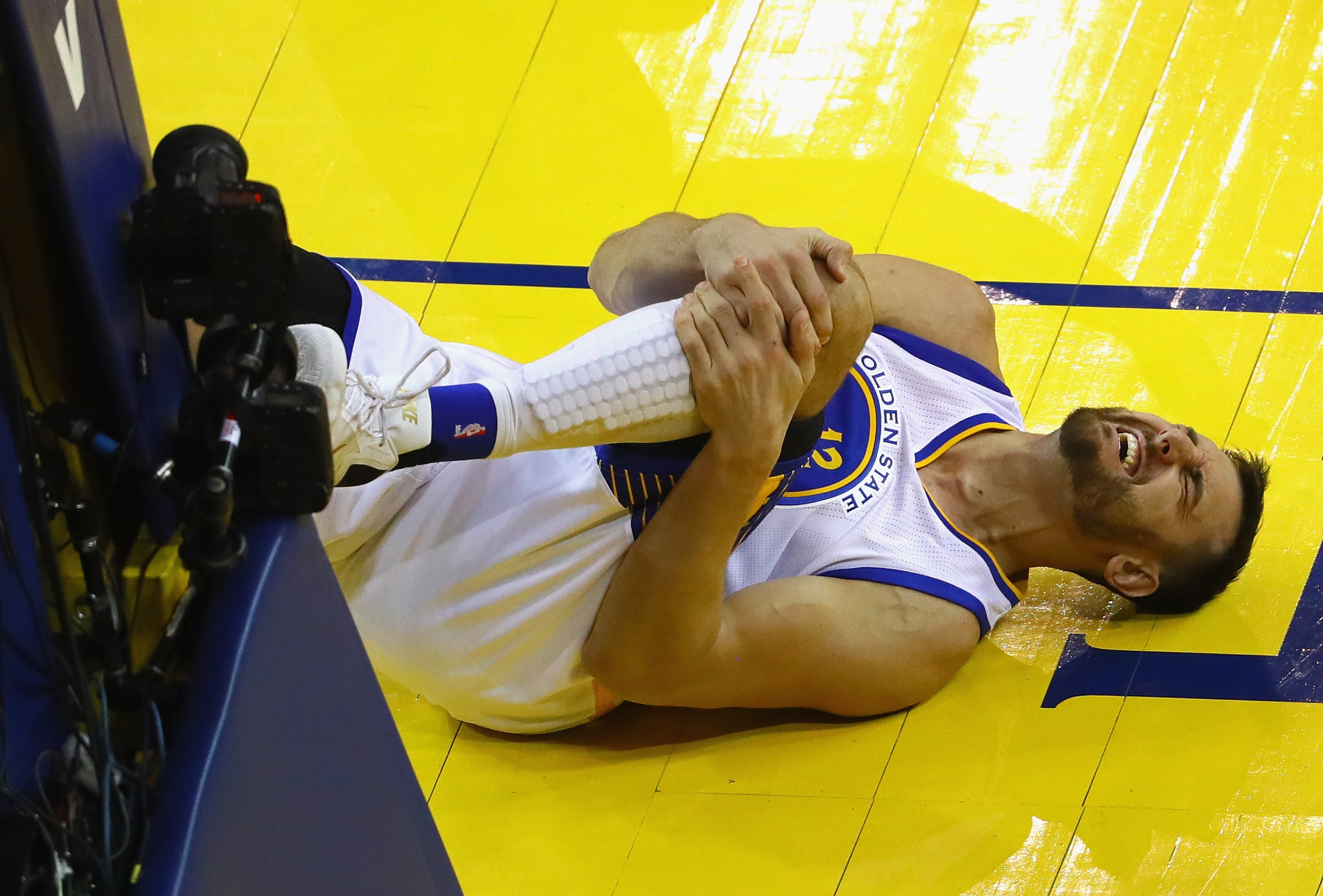OAKLAND, CA - JUNE 13:  Andrew Bogut #12 of the Golden State Warriors reacts after suffering an apparent injury during the second half against the Cleveland Cavaliers in Game 5 of the 2016 NBA Finals at ORACLE Arena on June 13, 2016 in Oakland, California