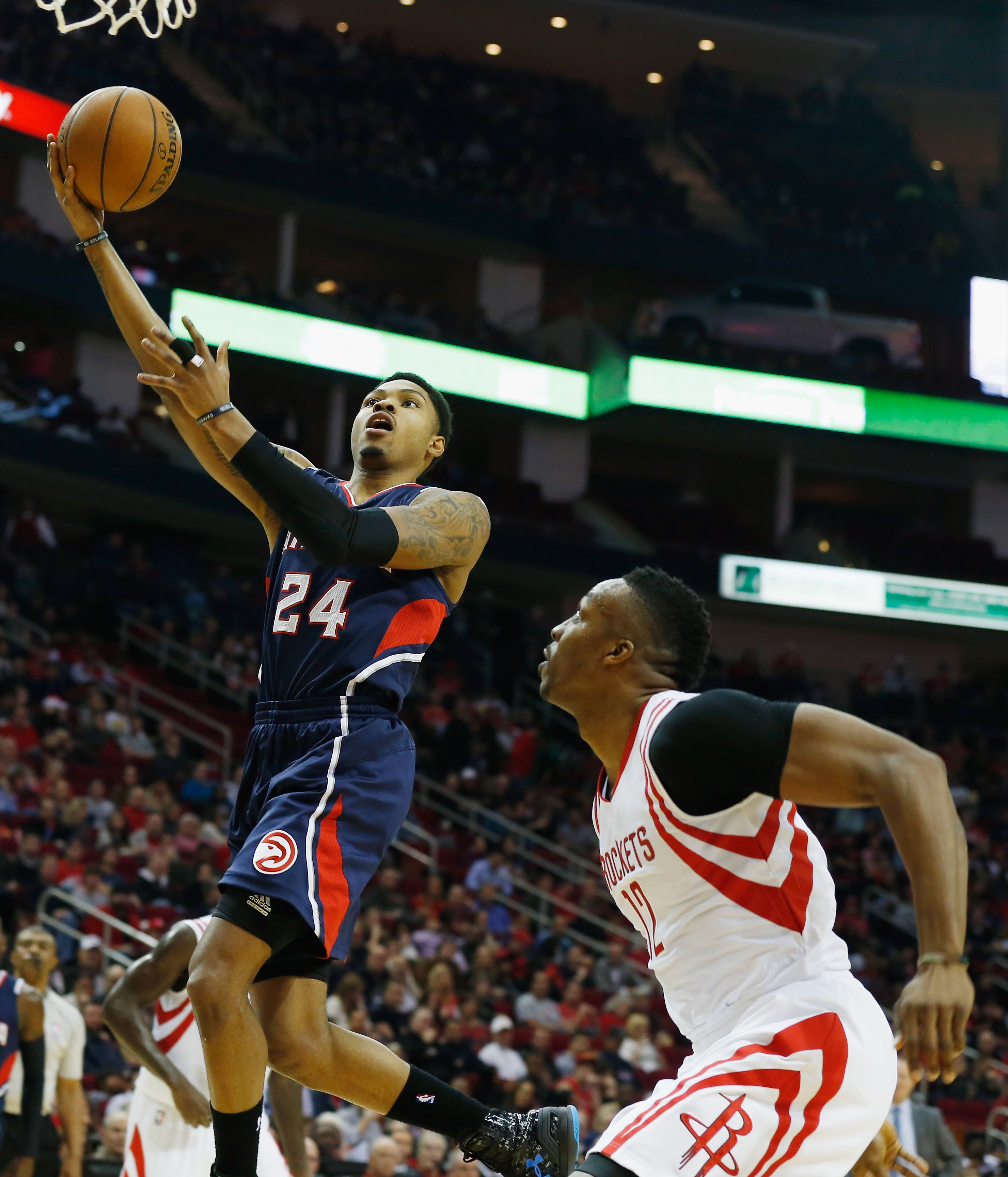 HOUSTON, TX - DECEMBER 20:  Kent Bazemore #24 of the Atlanta Hawks drives with the basketball past Dwight Howard #12 of the Houston Rockets during their game at the Toyota Center on December 20, 2014 in Houston, Texas.  (Photo by Scott Halleran/Getty Imag