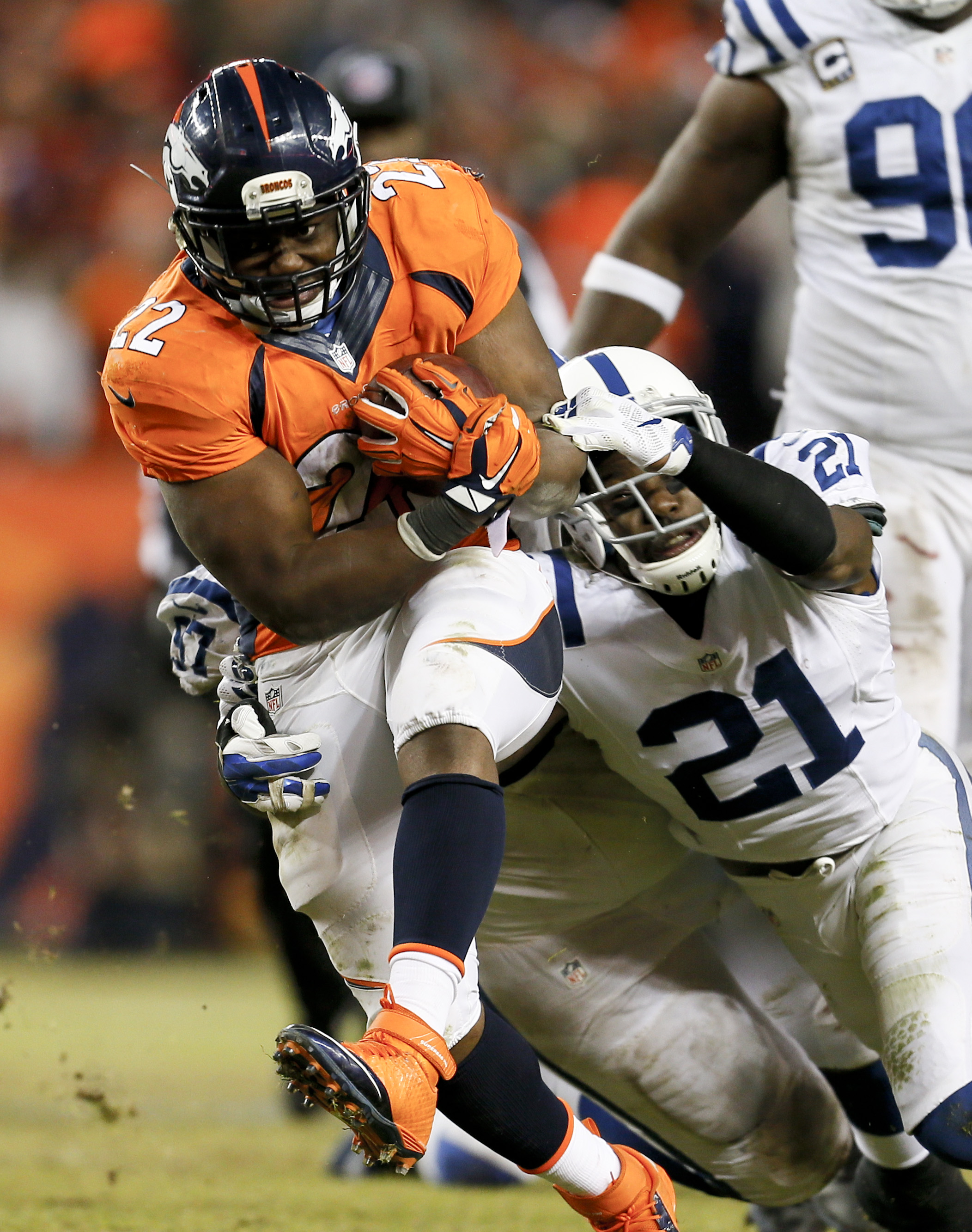 FILE - In this Jan. 11, 2015 file photo, Denver Broncos running back C.J. Anderson, left, converts a fourth down run for a first down as Indianapolis Colts cornerback Vontae Davis tries to tackle him from behind during the second half of an NFL divisional