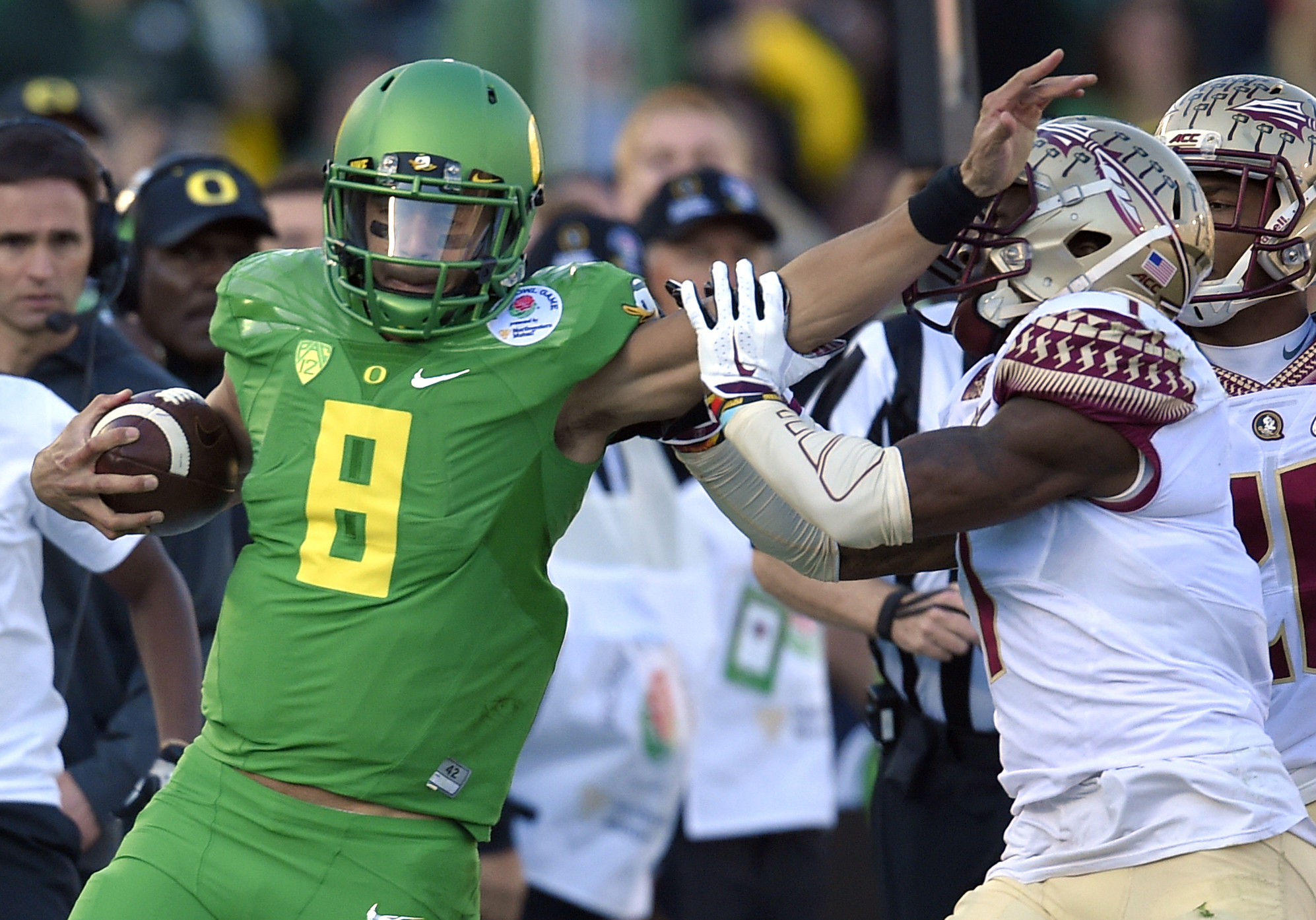 FILE- In this Jan. 1, 2015, file photo, Oregon quarterback Marcus Mariota, left, pushes away Florida State safety Tyler Hunter during the first half of the Rose Bowl NCAA college football playoff semifinal game in Pasadena, Calif. There will be several no