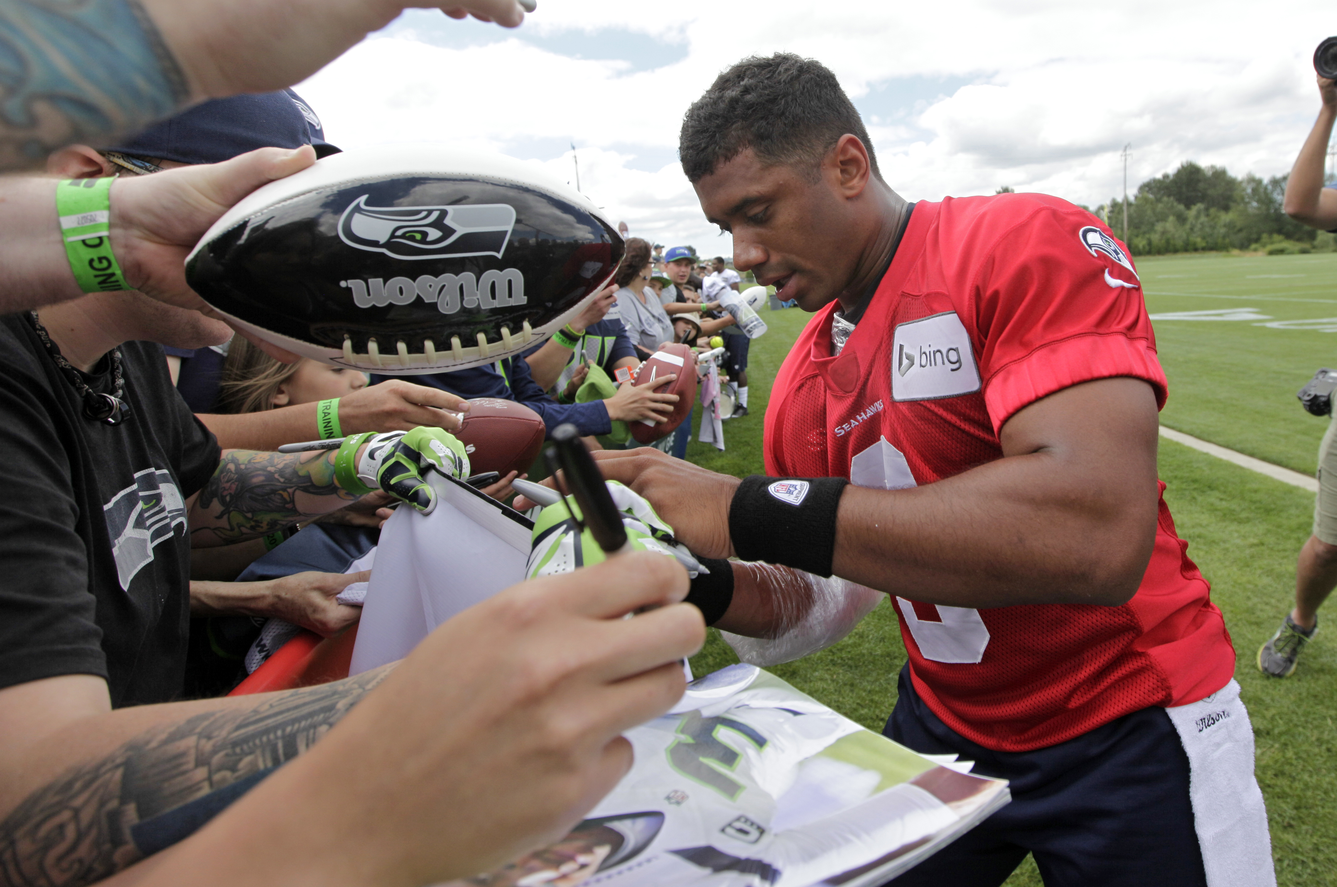 FILE - In this July 25, 2014, file photo, Seattle Seahawks quarterback Russell Wilson signs autographs following an NFL football camp practice in Renton, Wash. Wilson was taken in the third round of the 2012 Draft. He already has a Super Bowl ring. (AP Ph