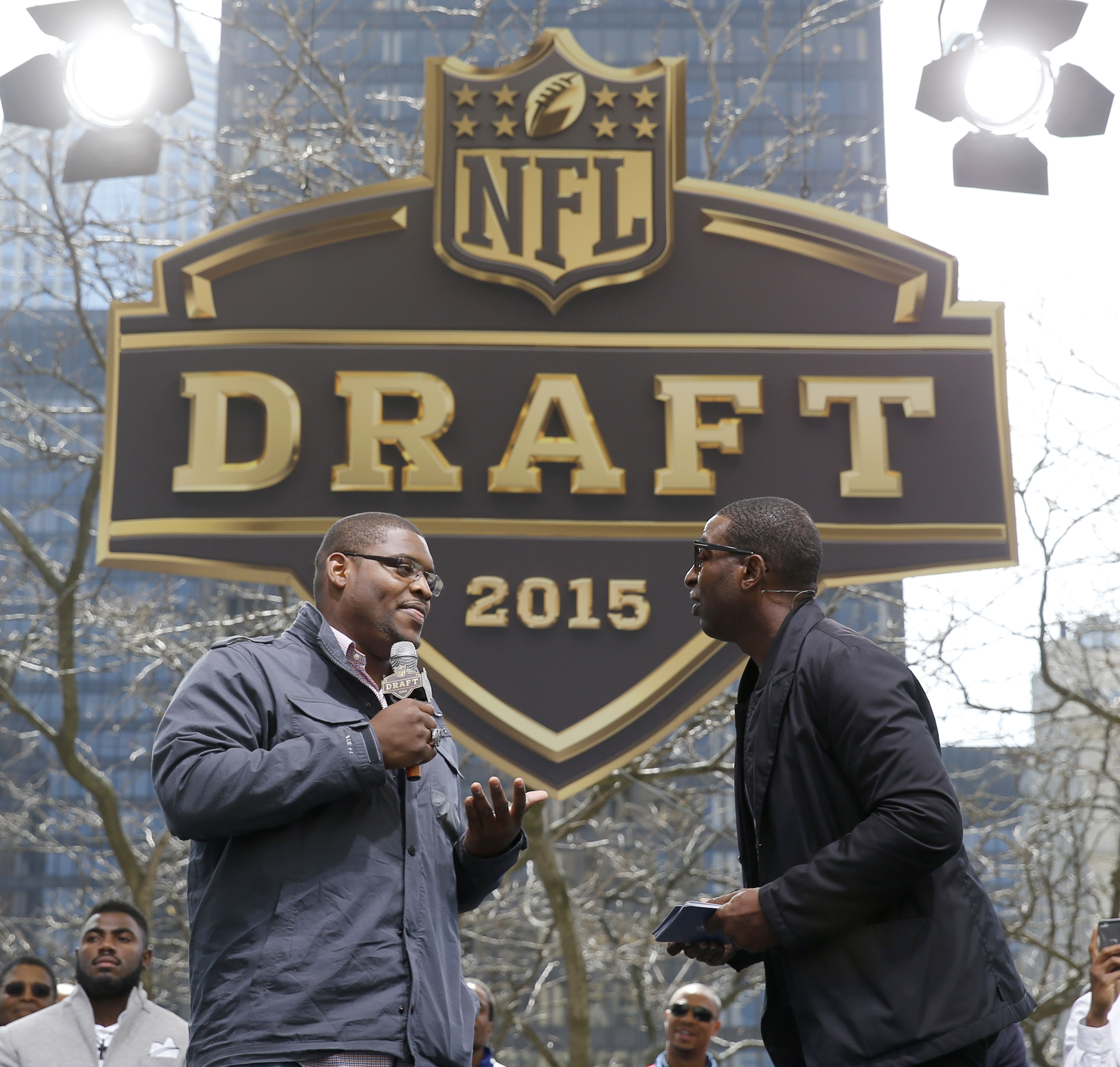 Cris Carter, right, interviews Duke's Laken Tomlinson, during introductions at a pre-draft rally of 2015 NFL Draft prospects, and various league legends at Pioneer Court, Wednesday, April 29, 2015, in Chicago. (AP Photo/Charles Rex Arbogast)