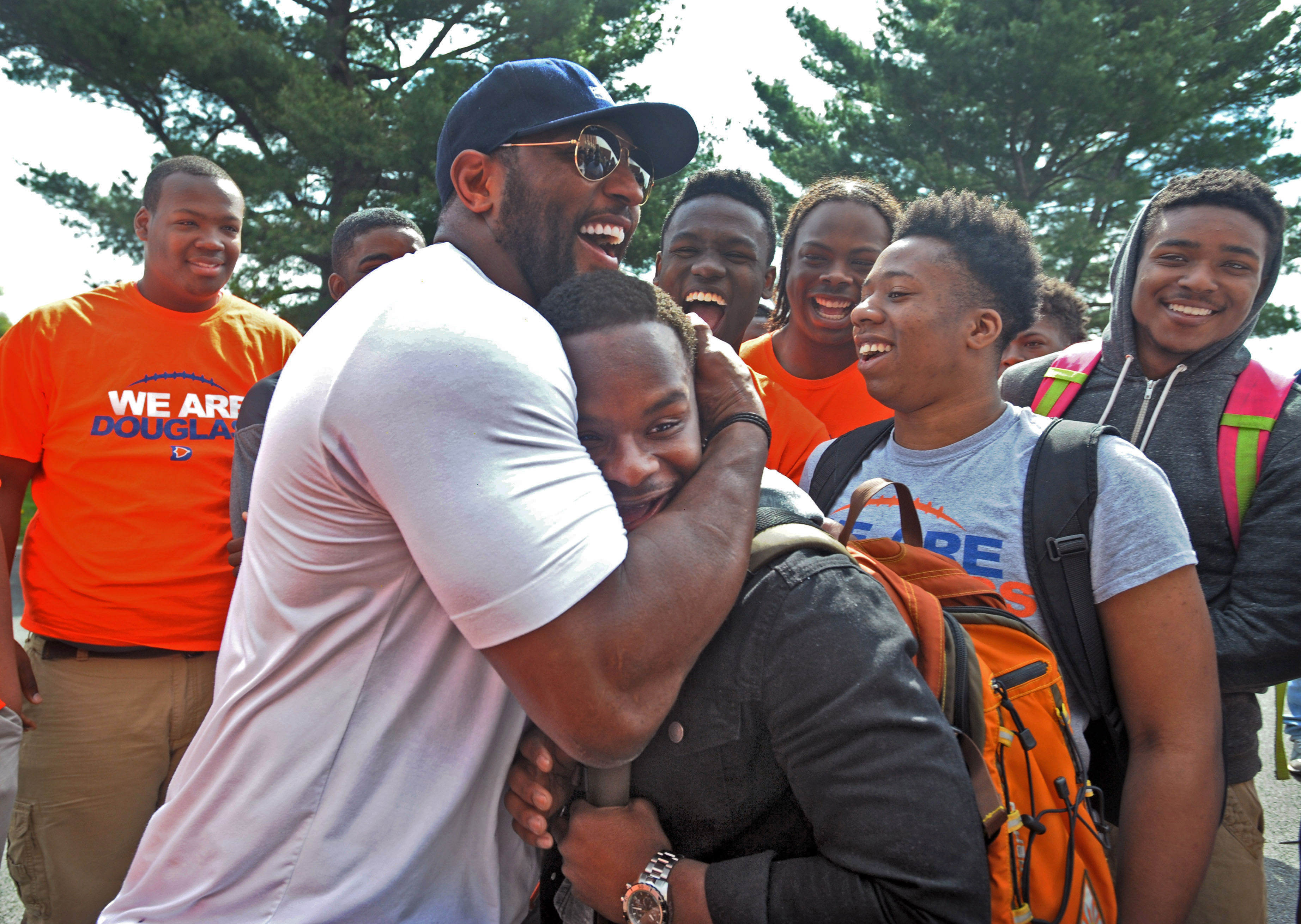 Former Baltimore Ravens NFL football player Ray Lewis hugs 17-year-old Azariah Bratton-Bey Jr., a senior running back on Frederick Douglass High's football team, during a visit to the school Thursday, April 30, 2015, in Baltimore. Lewis, Ravens coach John