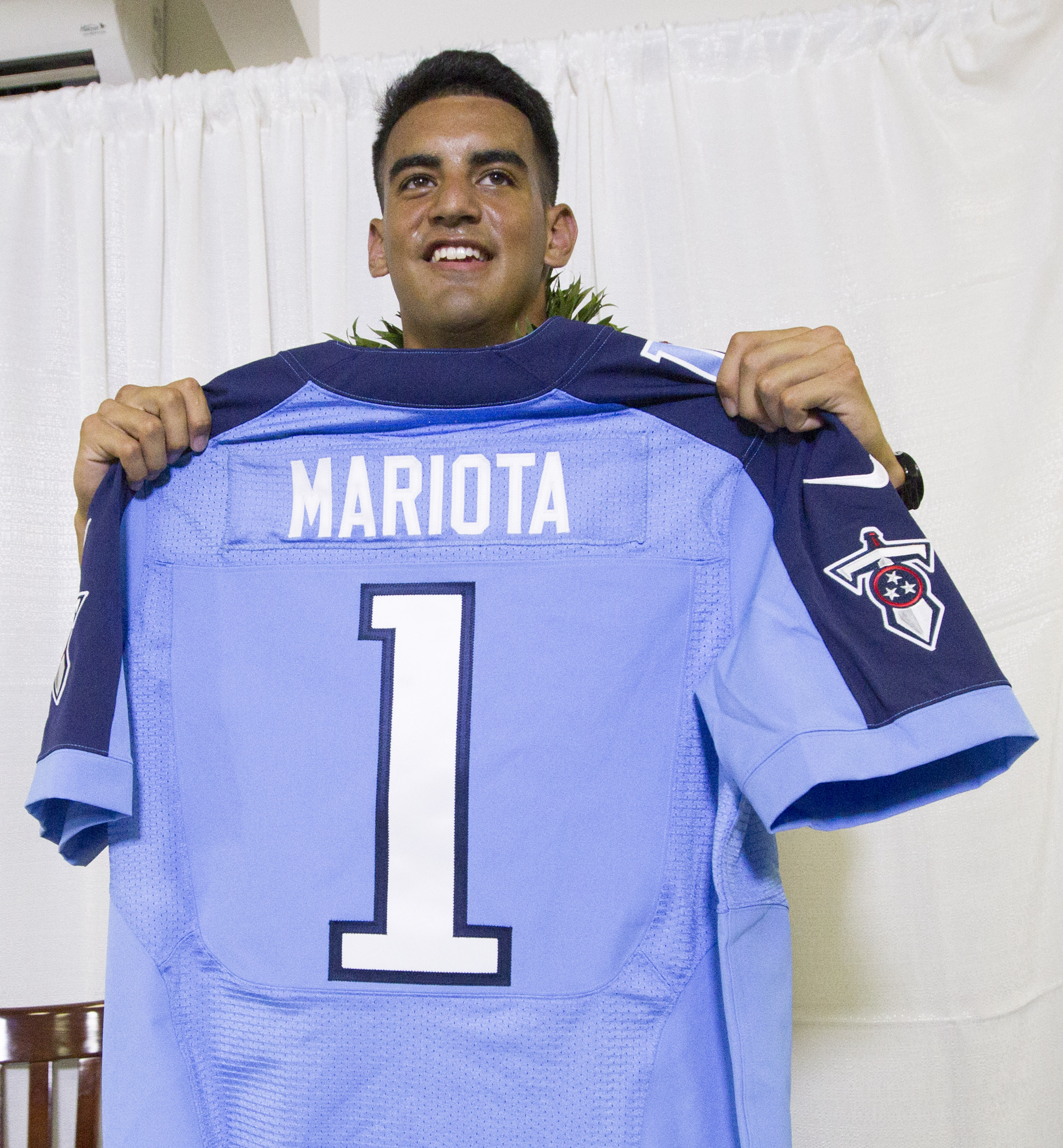 Former Oregon quarterback Marcus Mariota holds up his Tennessee Titians jersey for the media after being selected in the first round with the second pick by the Tennessee Titans on NFL Draft Day Thursday, April 30, 2015, in Honolulu. Mariota along with hi