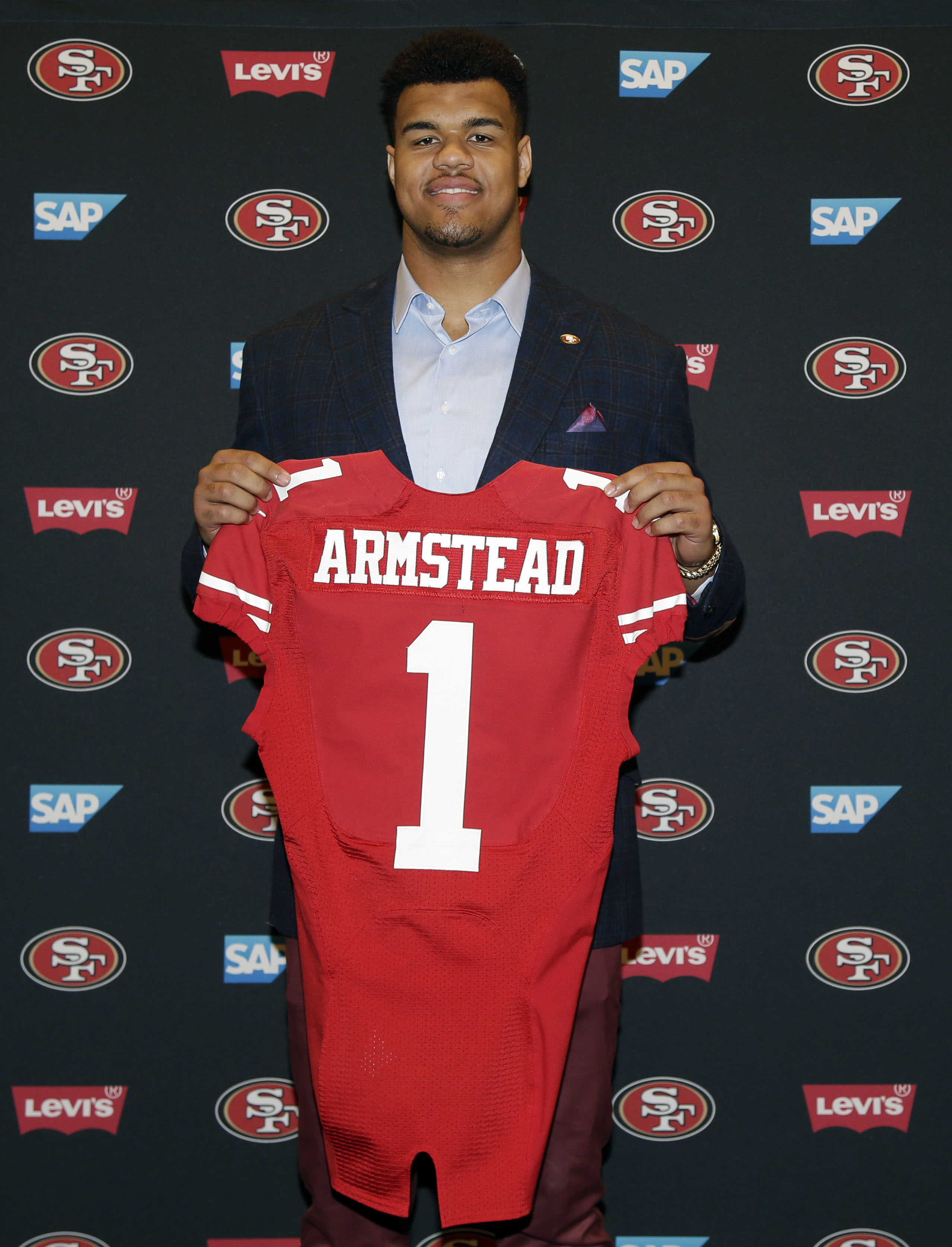 San Francisco 49ers first-round draft pick Arik Armstead holds up a jersey during an NFL football news conference Friday, May 1, 2015, in Santa Clara, Calif. (AP Photo/Marcio Jose Sanchez)