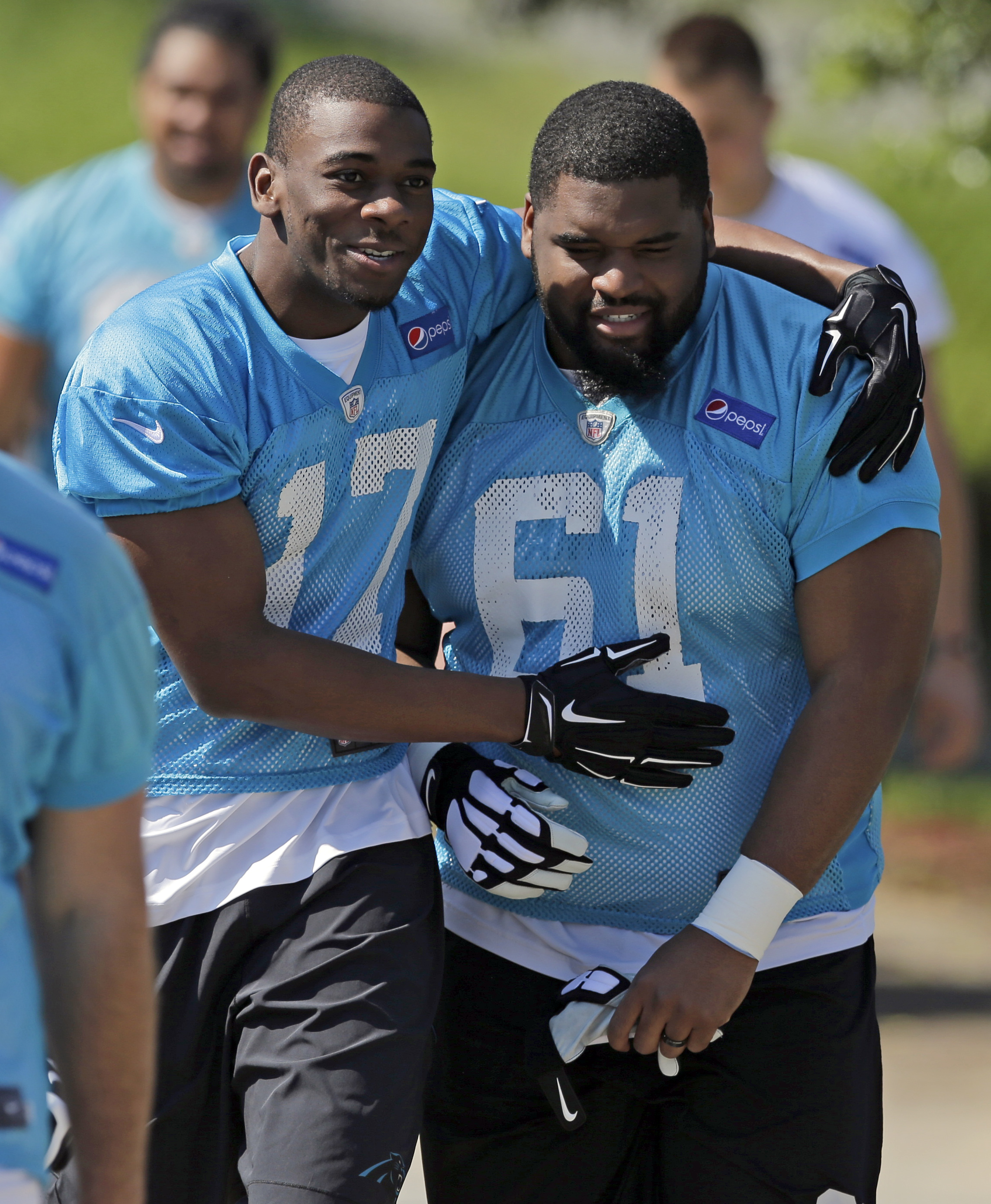 Carolina Panthers' Devin Funchess (17) jokes with Zach Allen (61) as they walk to a practice at the NFL football team's rookie minicamp in Charlotte, N.C., Friday, May 8, 2015. (AP Photo/Chuck Burton)