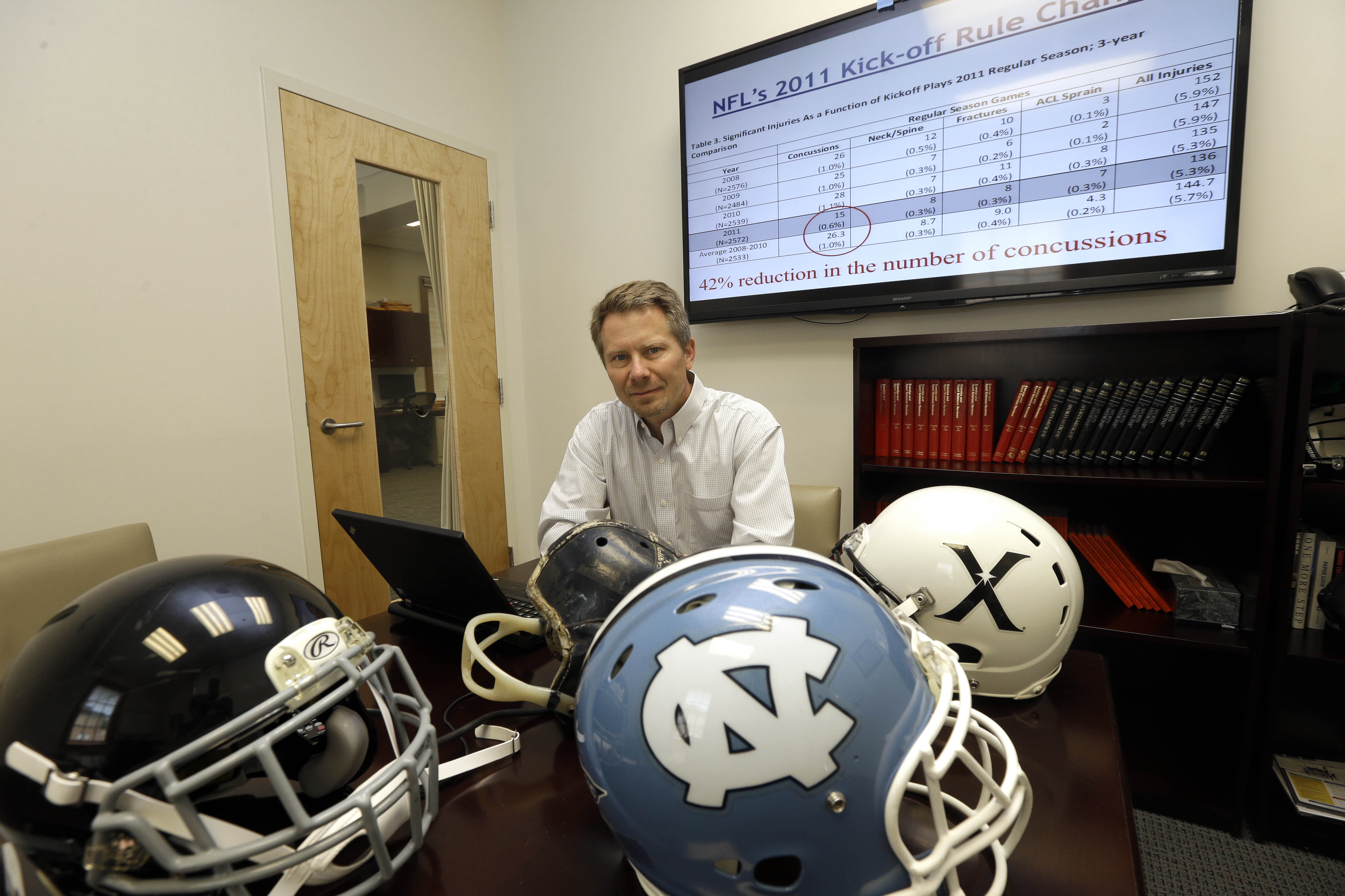 ADVANCE FOR WEEKEND EDITIONS, MAY 15-17 - In this photo taken Wednesday, May 13, 2015, Kevin Guskiewicz, professor and former chair of the Department of Exercise and Sports Medicine at the College of Arts and Sciences, is surrounded by football helmets wh