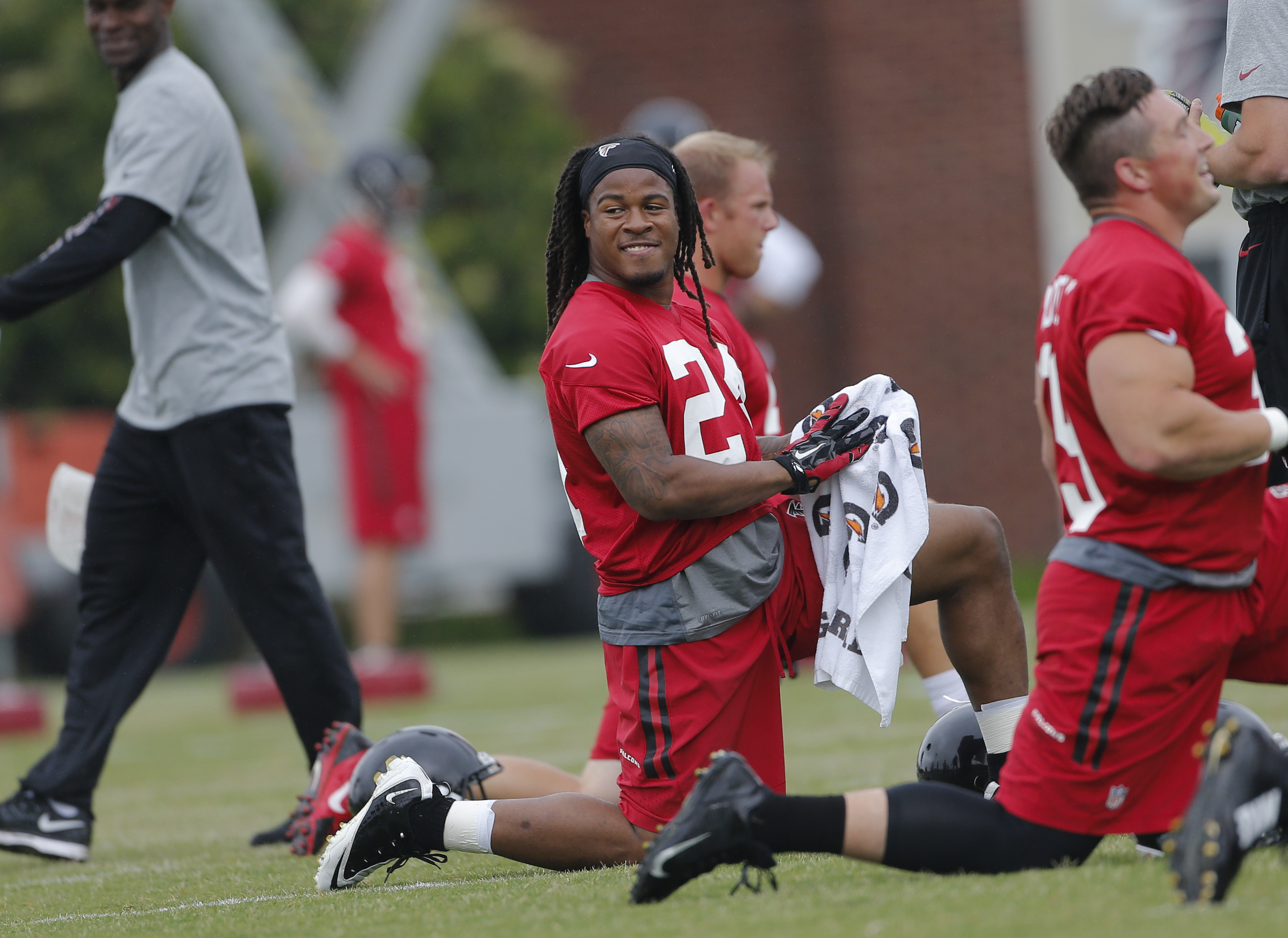 Atlanta Falcons running back Devonta Freeman (24) stretches during an offseason NFL football  training session Tuesday, May 26, 2015, in Flowery Branch, Ga.  (AP Photo/John Bazemore)