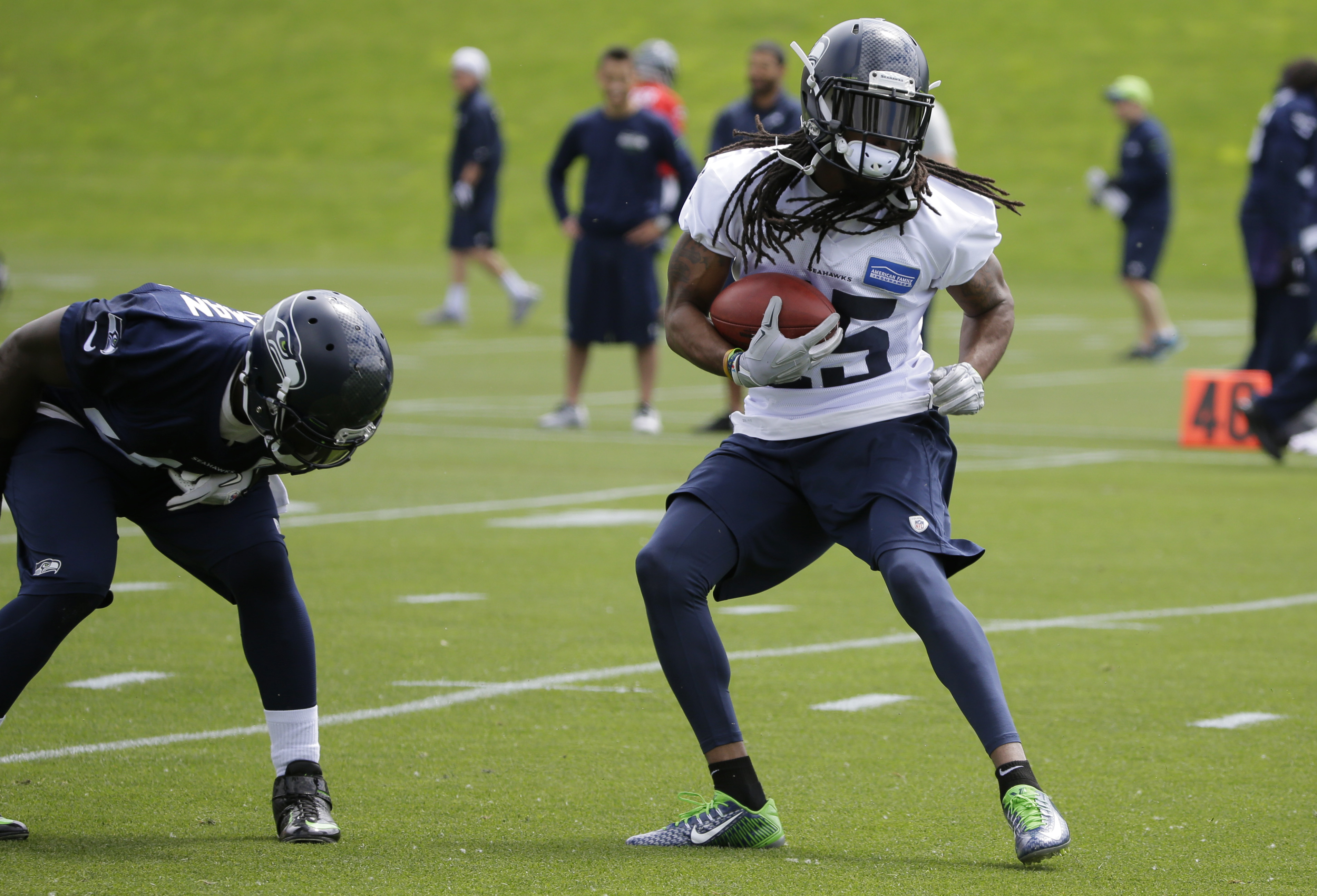 Seattle Seahawks cornerback Richard Sherman, right, playfully jukes around fullback Derrick Coleman, left, as he runs with the ball during an organized team activity Tuesday, May 26, 2015, in Renton, Wash. (AP Photo/Ted S. Warren)