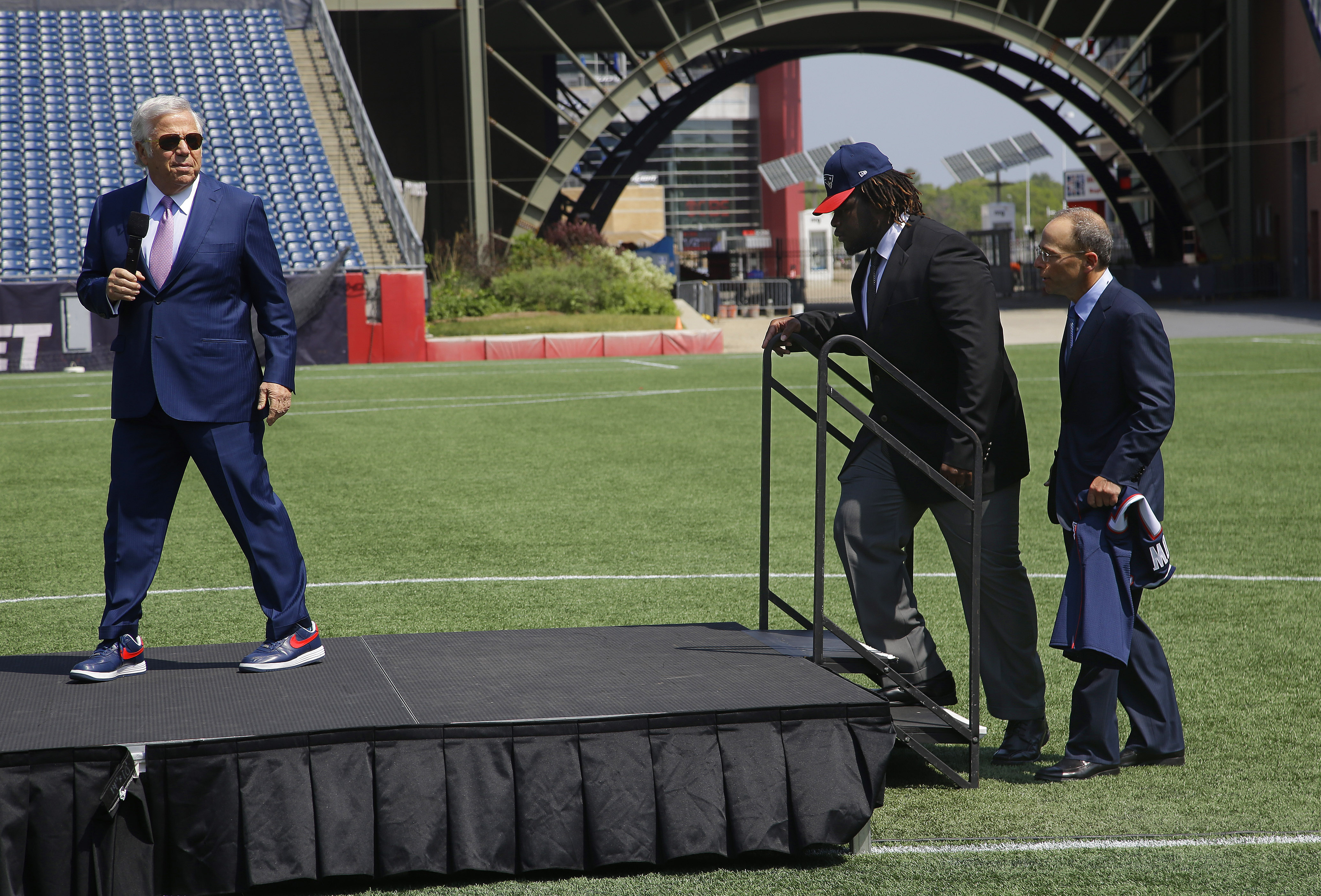 Defensive lineman Malcom Brown, second from left, the New England Patriots first round draft pick, takes the stage as Patriots owner Robert Kraft prepares to introduce Brown during a media availability at the NFL football team's facility Wednesday, May 27