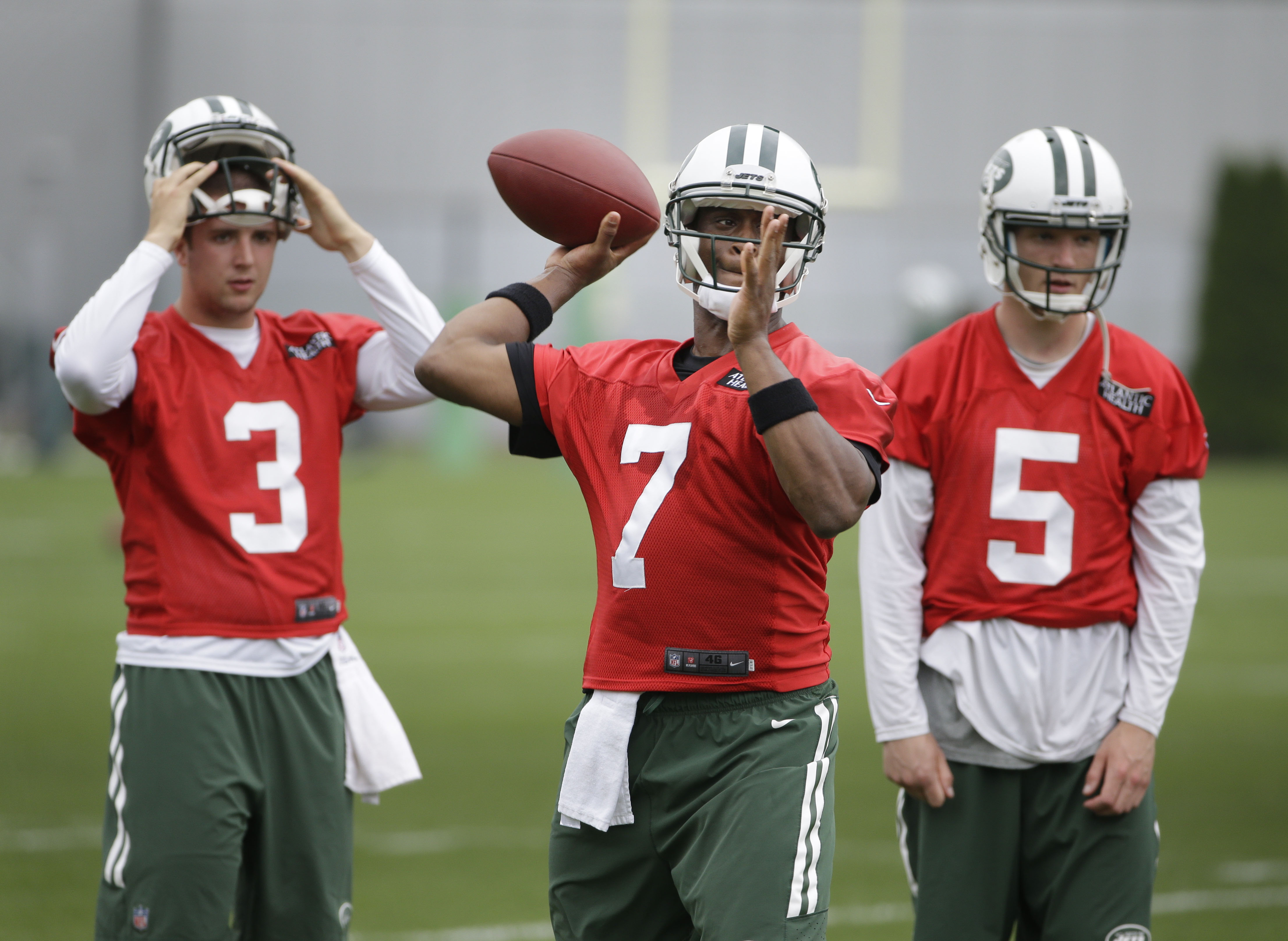 New York Jets quarterback Geno Smith (7) throws a pass during an NFL football organized team activity in Florham Park, N.J., Wednesday, May 27, 2015. Quarterbacks Matt Simms (5) and Jake Heaps (3) watch. (AP Photo/Seth Wenig)
