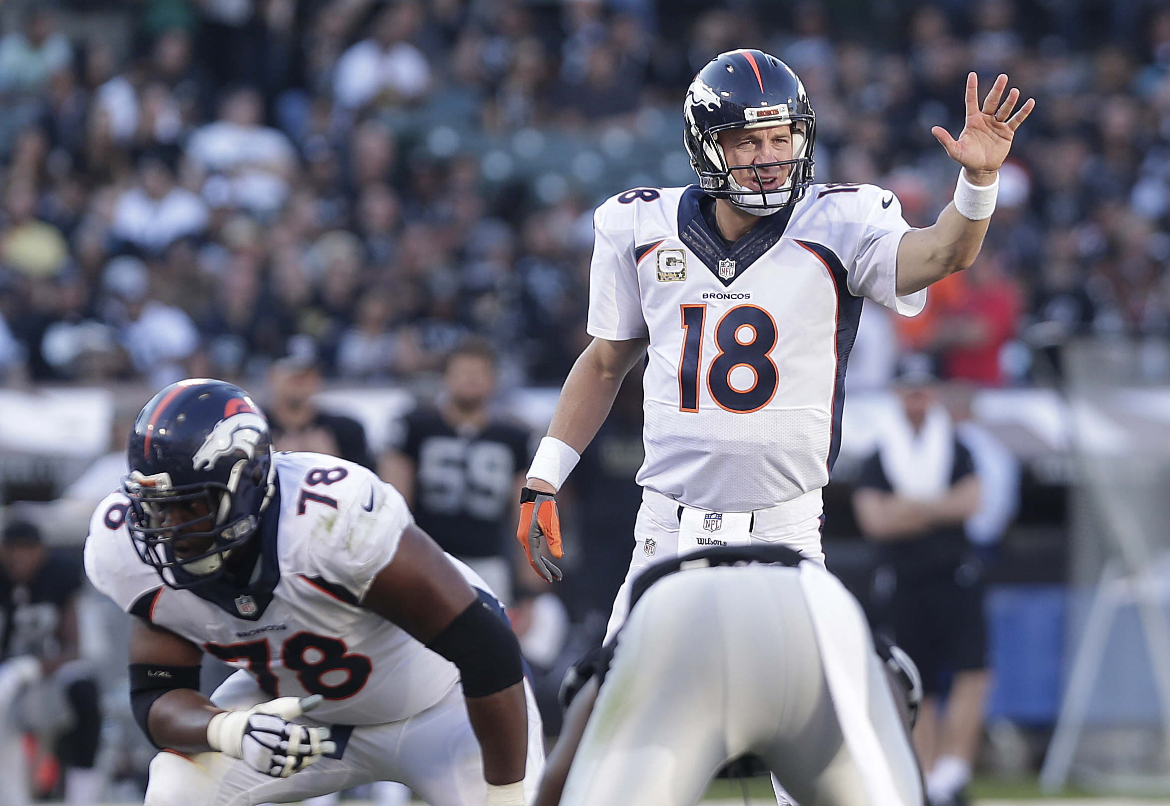 Denver Broncos quarterback Peyton Manning (18) signals at the line of scrimmage behind offensive tackle Ryan Clady (78) against the Oakland Raiders during the third quarter of an NFL football game in Oakland, Calif., Sunday, Nov. 9, 2014. (AP Photo/Marcio