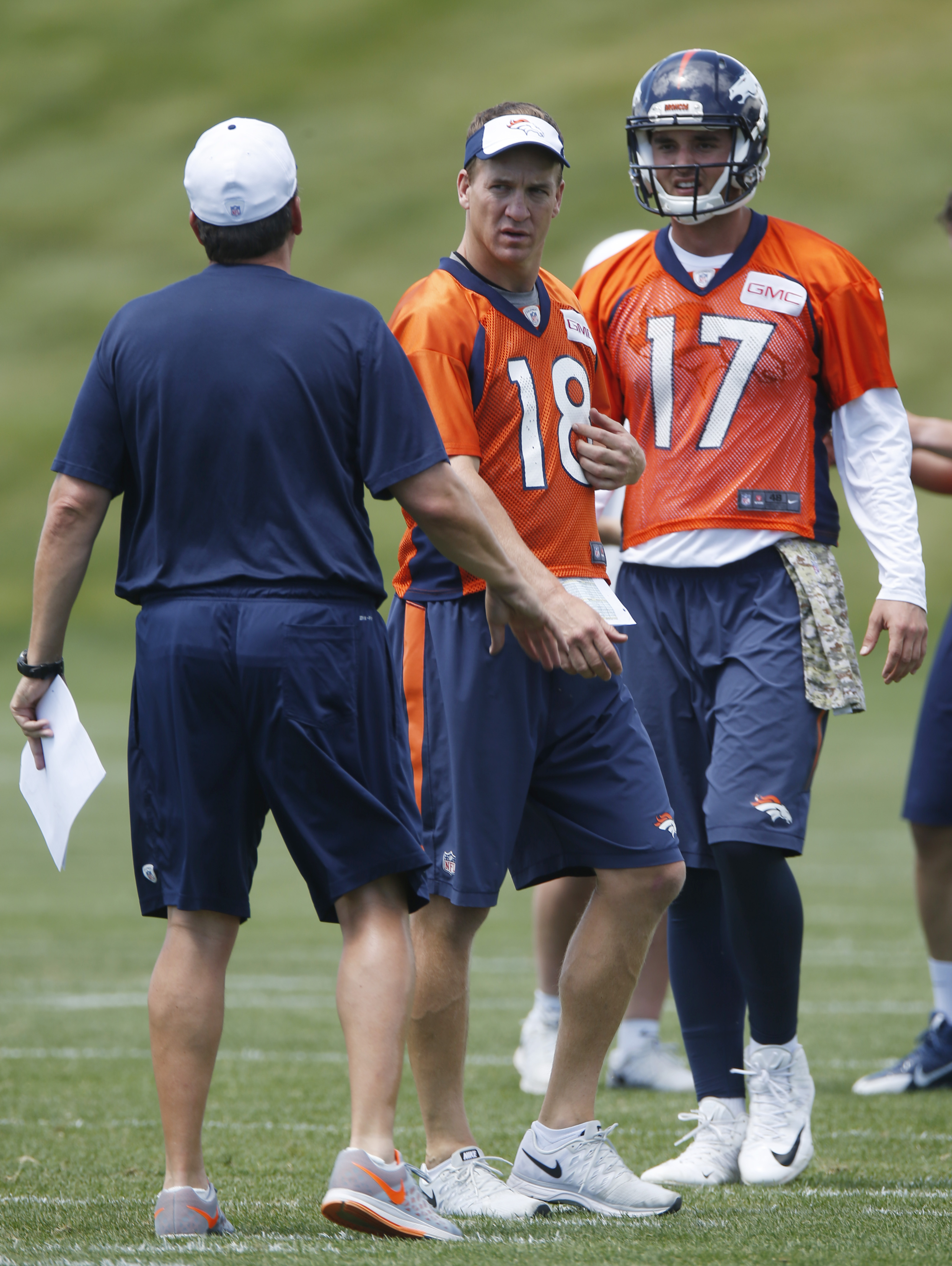 Denver Broncos quarterbacks Peyton Manning, center, and Brock Osweiler, back, confer with quarterbacks coach Greg Knapp during an organized training activity at the team's headquarters in Englewood, Colo., Monday, June 1, 2015. (AP Photo/David Zalubowski)