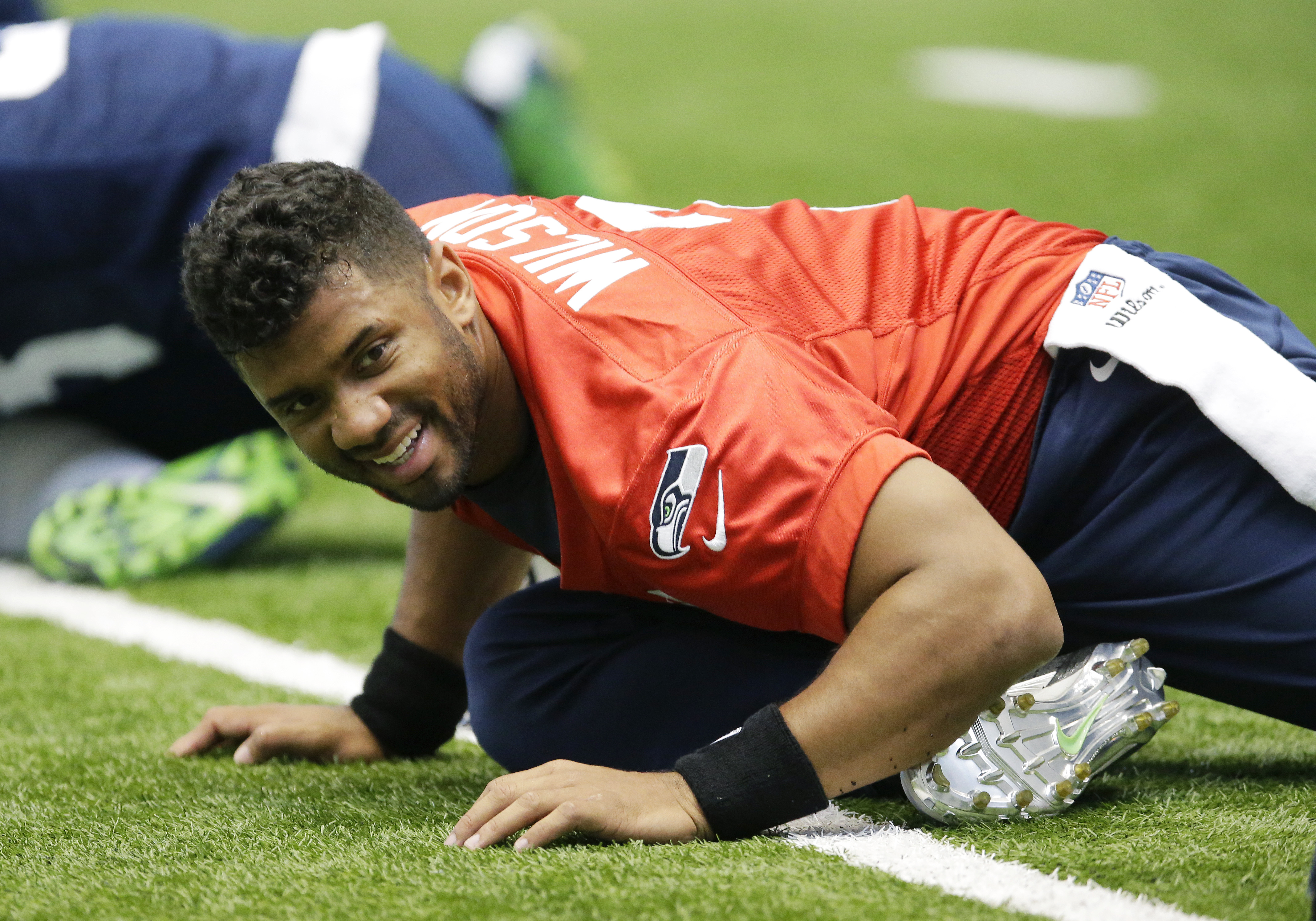 Seattle Seahawks quarterback Russell Wilson smiles as he stretches with teammates before an organized team activity, Tuesday, June 2, 2015, in Renton, Wash. (AP Photo/Ted S. Warren)