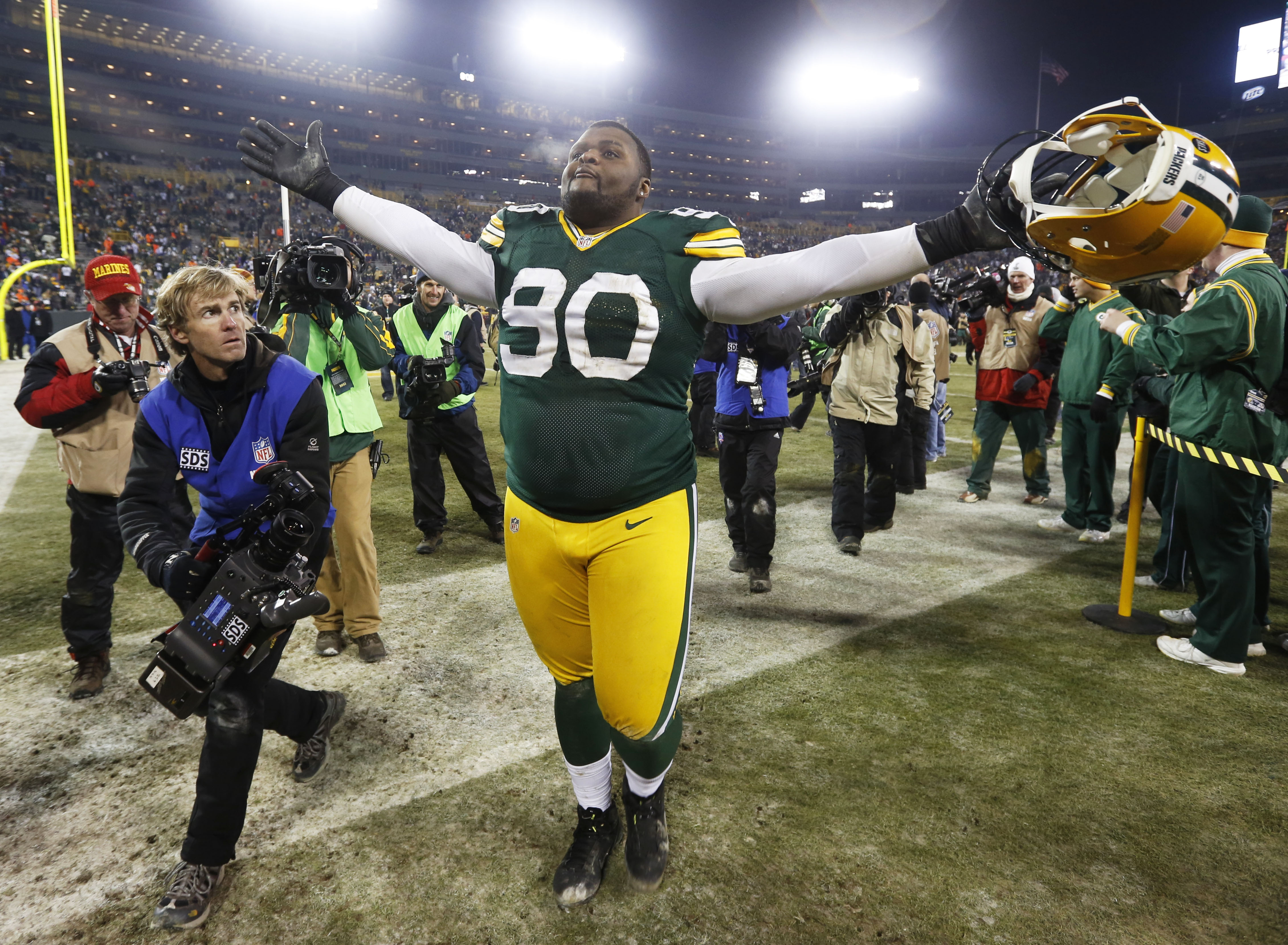 FILE - In this January, 2013 file photo, Green Bay Packers nose tackle B.J. Raji (90) celebrates after an NFL wild card playoff football game against the Minnesota Vikings in Green Bay, Wis. Veterans Julius Peppers and Raji are back to fortify the Packers