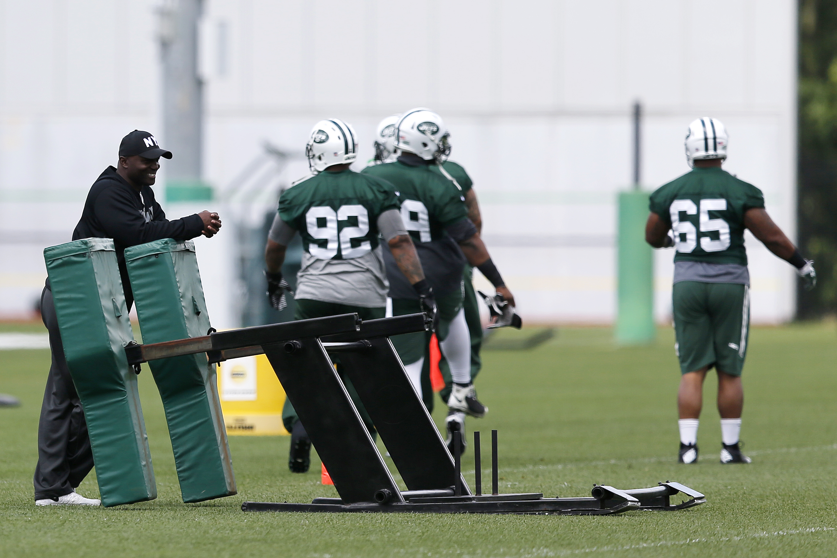 New York Jets head coach Todd Bowles, left, looks on as defensive players warm up during organized team activities at the team's NFL football training center, Wednesday, June 3, 2015, in Florham Park, N.J. (AP Photo/Julio Cortez)