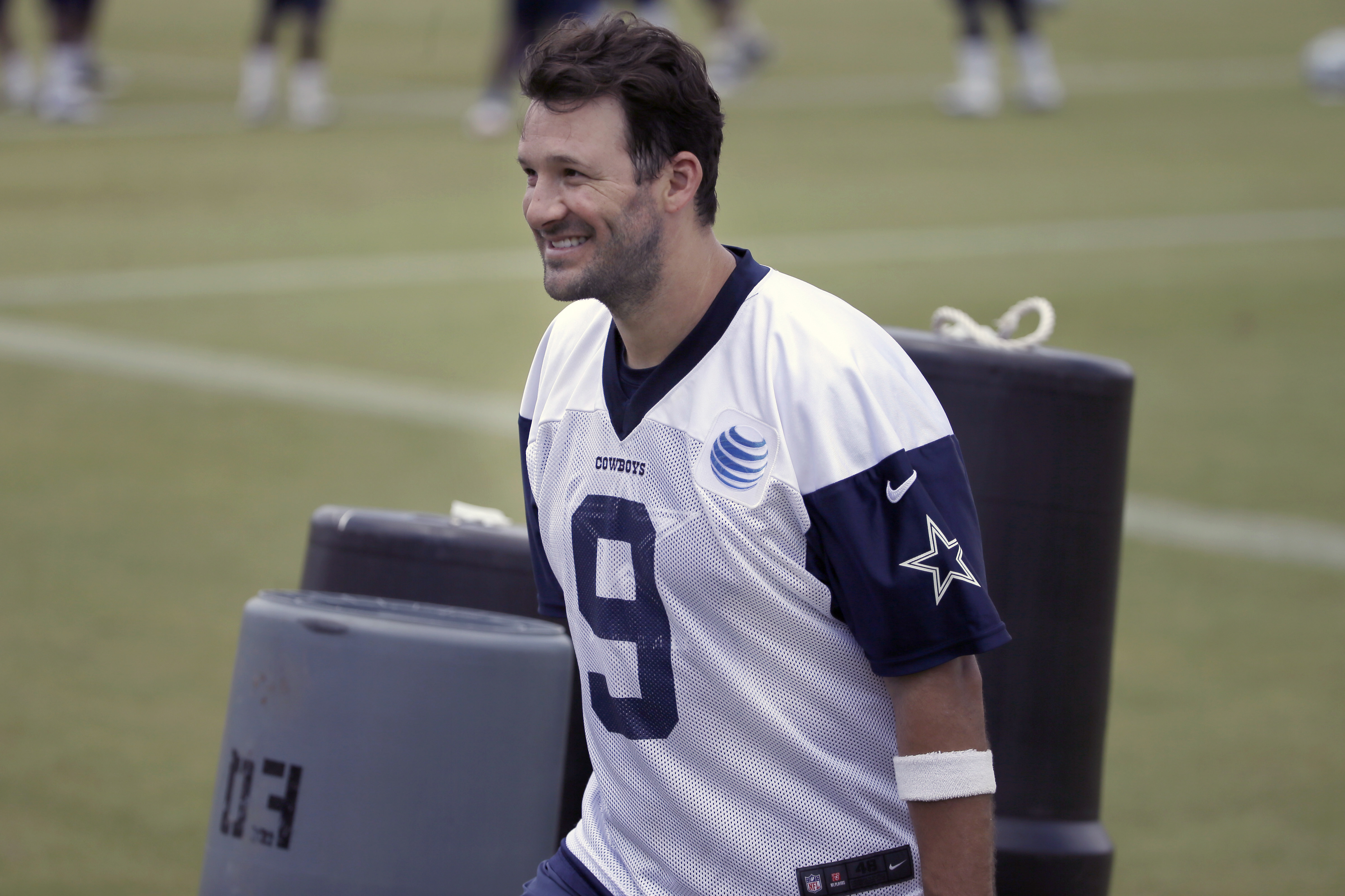 Dallas Cowboys quarterback Tony Romo smiles as he walks off the filed during an NFL football organized team activity,  Wednesday, June 3, 2015, in Irving, Texas. (AP Photo/LM Otero)