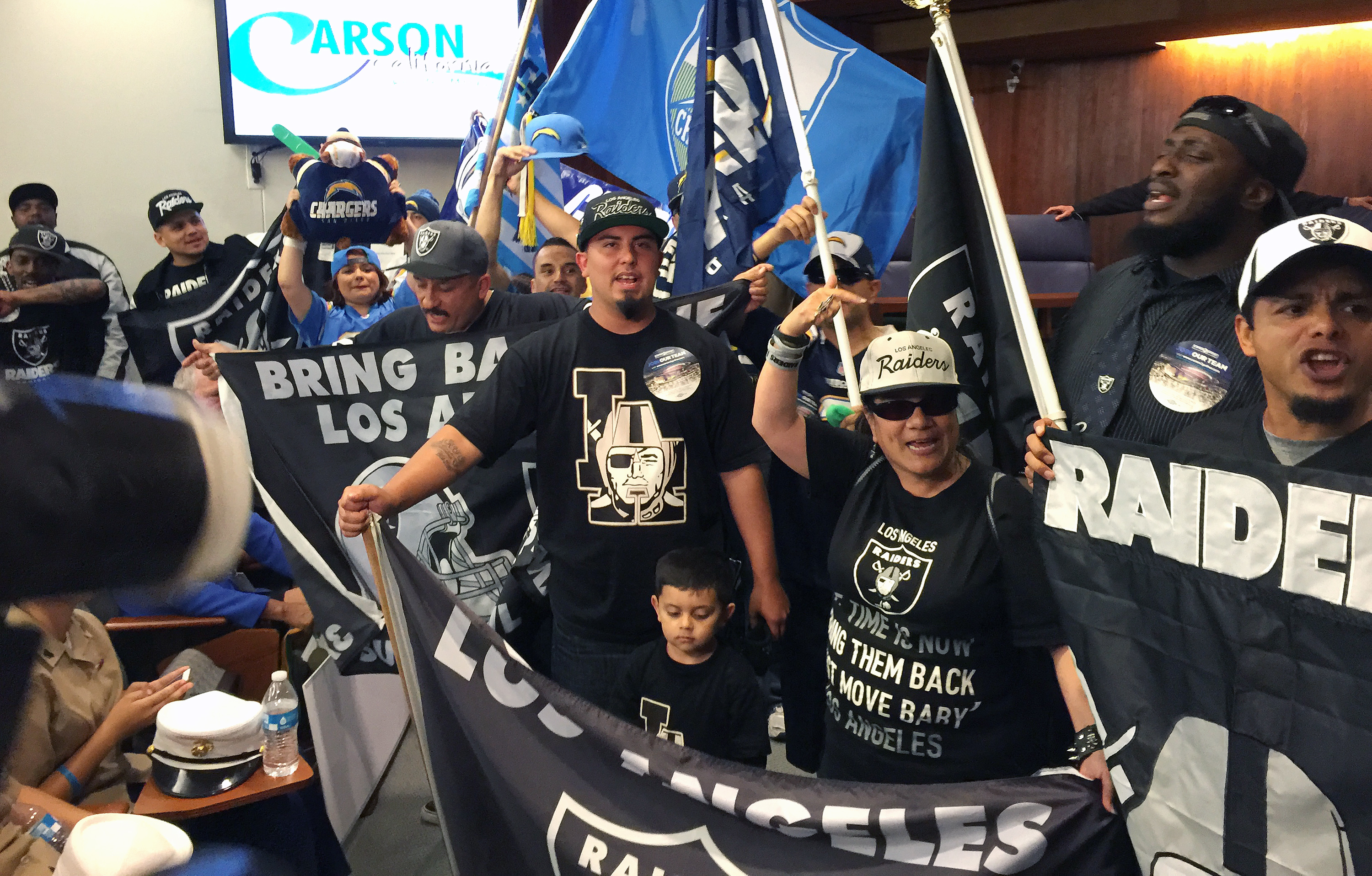 """In this photo taken Tuesday, April 21, 2015, football fans, who want to see an NFL team return to the Los Angeles area after two decades, chant """" bring them back!"""" before a Carson City Council vote on whether to approve the plan to build an NFL football s"""