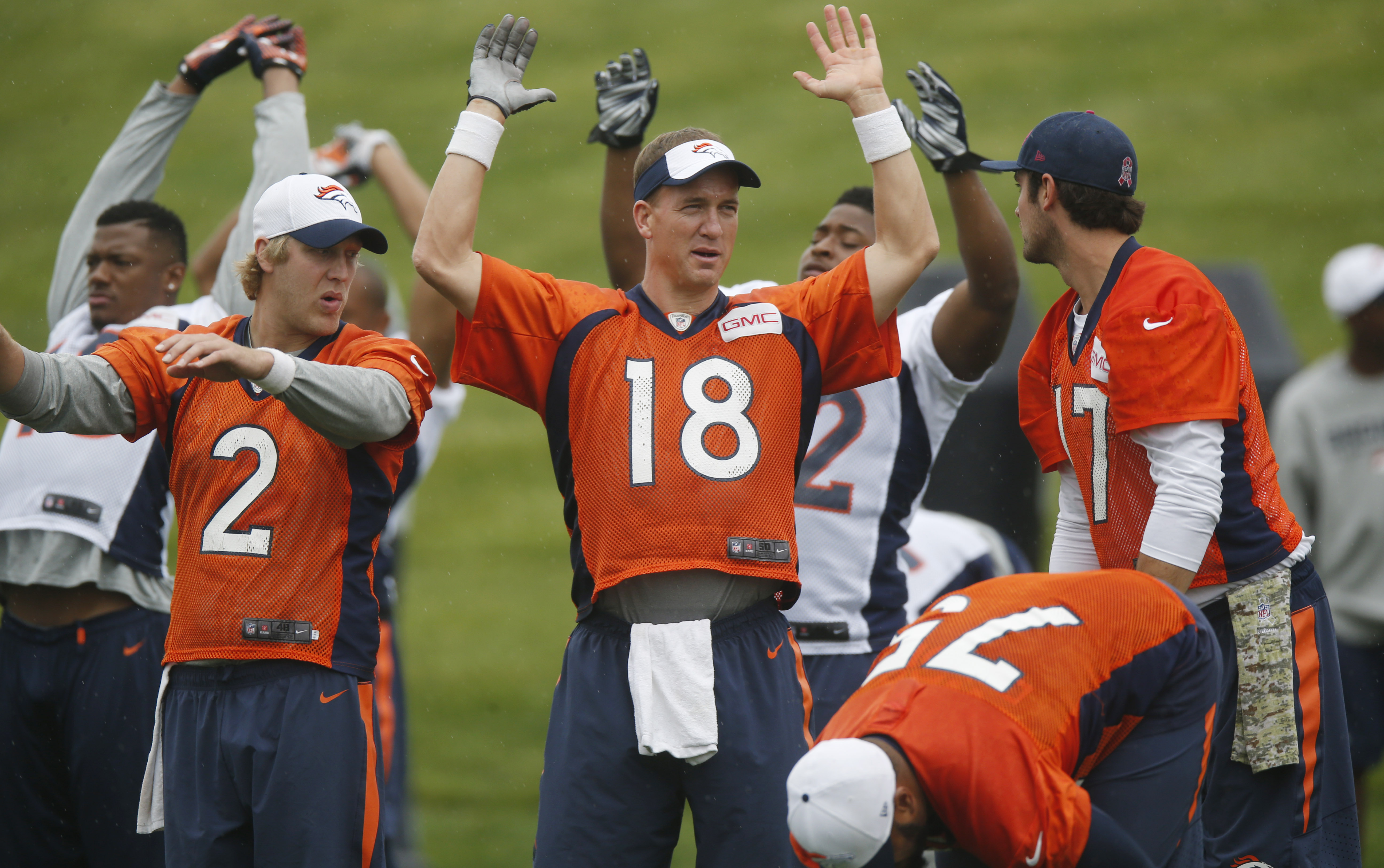 Denver Broncos quarterbacks Peyton Manning, center, Brock Osweiler, right, and Zac Dysert chat during NFL football minicamp at the team's headquarters, Wednesday, June 10, 2015, in Englewood, Colo. (AP Photo/David Zalubowski)