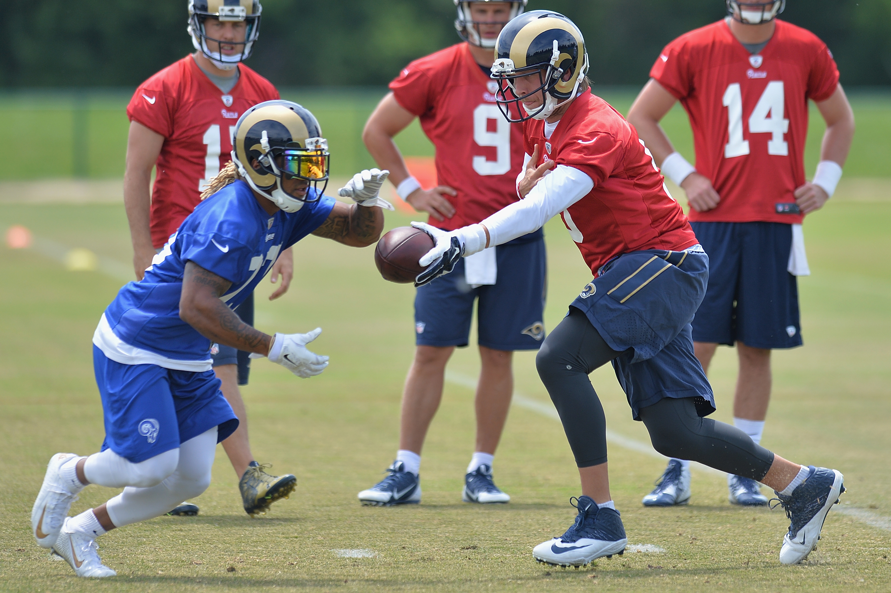 St. Louis Rams quarterback Nick Foles, right, hands the ball off to running back Tre Mason, left, during an NFL football organized team activity, Thursday, June 11, 2015, in St. Louis. (AP Photo/Michael Thomas)