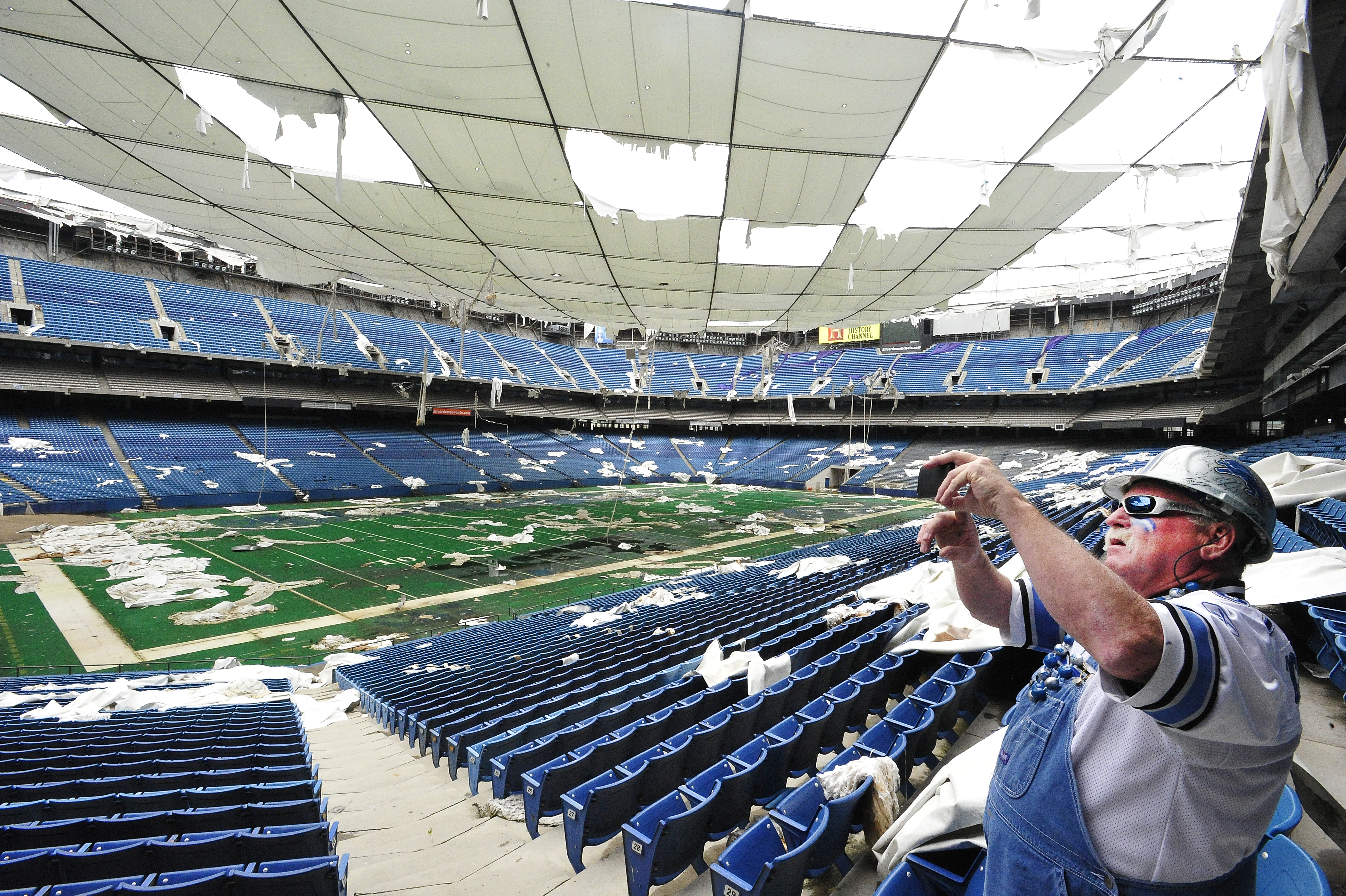 """FILE - In this May 12, 2014 file photo,   Ron """"Crackman"""" Crachiola takes a picture on his cell phone at the Pontiac Silverdome in Pontiac,  Mich.  The Pontiac Silverdome is up for sale again, with an asking price of about $30 million. The former home of t"""