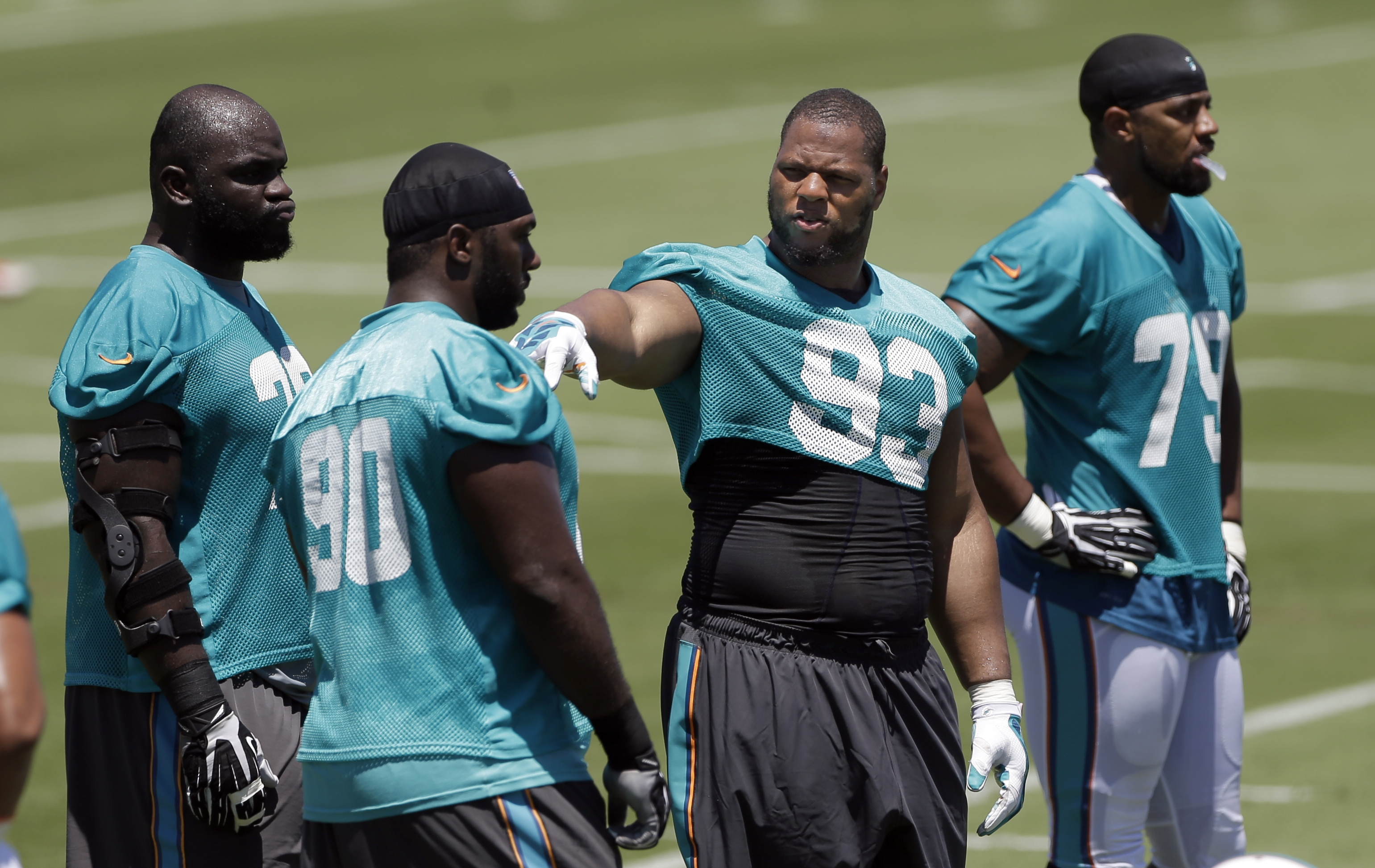 Miami Dolphins defensive tackle Ndamukong Suh (3) gestures as he talks to Earl Mitchell (90) during NFL football minicamp, Tuesday, June 16, 2015, in Davie, Fla. (AP Photo/Alan Diaz)