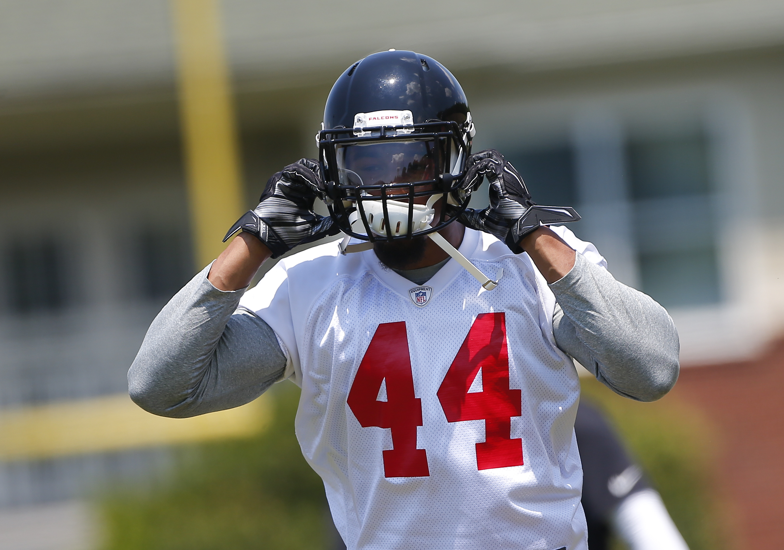 FILE - In this May 8, 2015, file photo, Atlanta Falcons first round pick Vic Beasley adjusts his helmet during the first day of NFL football rookie minicamp  in Flowery Branch, Ga. Beasley has had a busy, productive week. First he signed a $14.5 million c