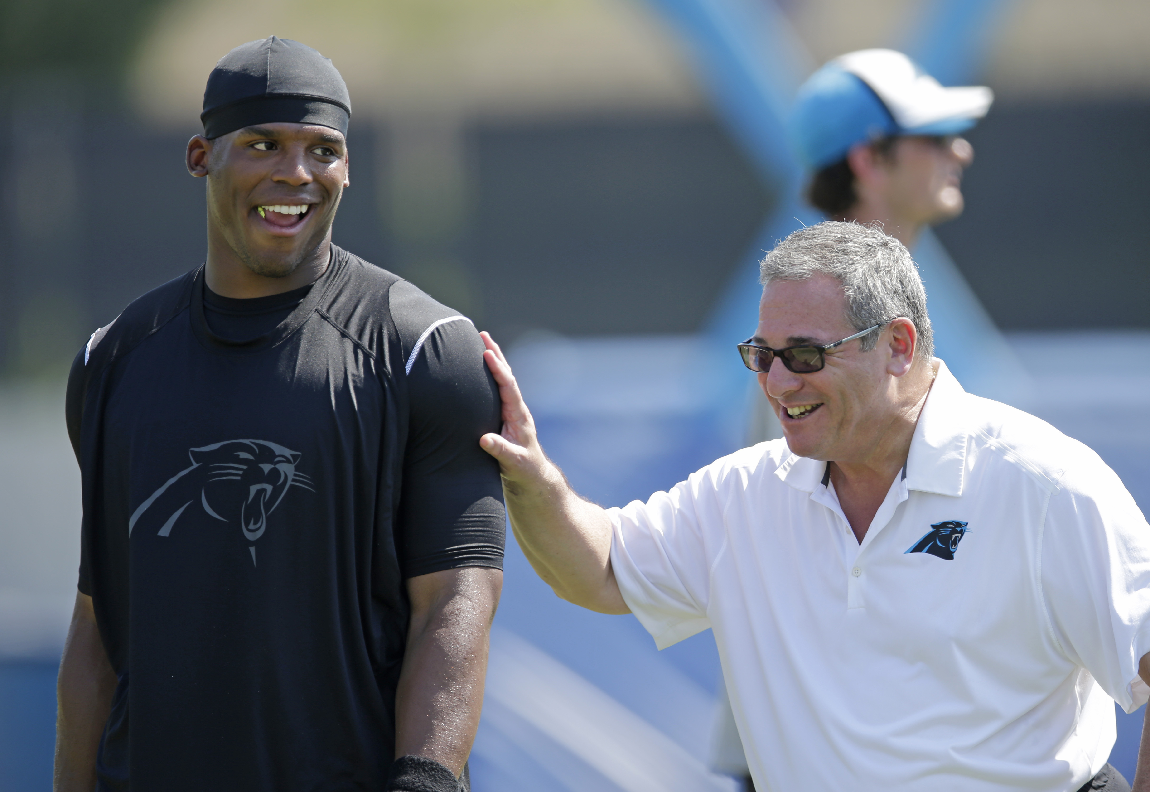 Carolina Panthers' Cam Newton, left, shares a laugh with general manager Dave Gettleman, right, after a practice during the NFL team's minicamp in Charlotte, N.C., Thursday, June 18, 2015. (AP Photo/Chuck Burton)