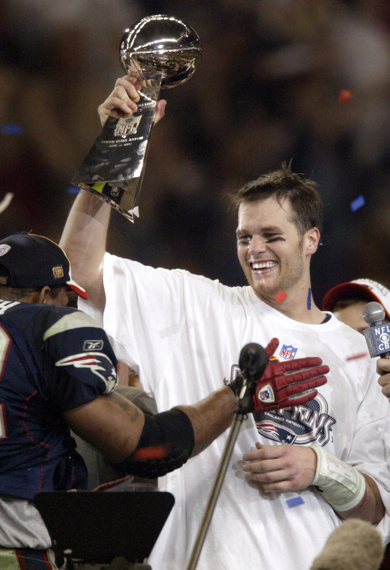 FILE - In this Feb. 1, 2004, file photo, New England Patriots quarterback Tom Brady, right, celebrates with the Vince Lombardi trophy after the Patriots defeated the Carolina Panthers 32-29 in NFL football's Super Bowl XXXVIII in Houston. Brady grew from