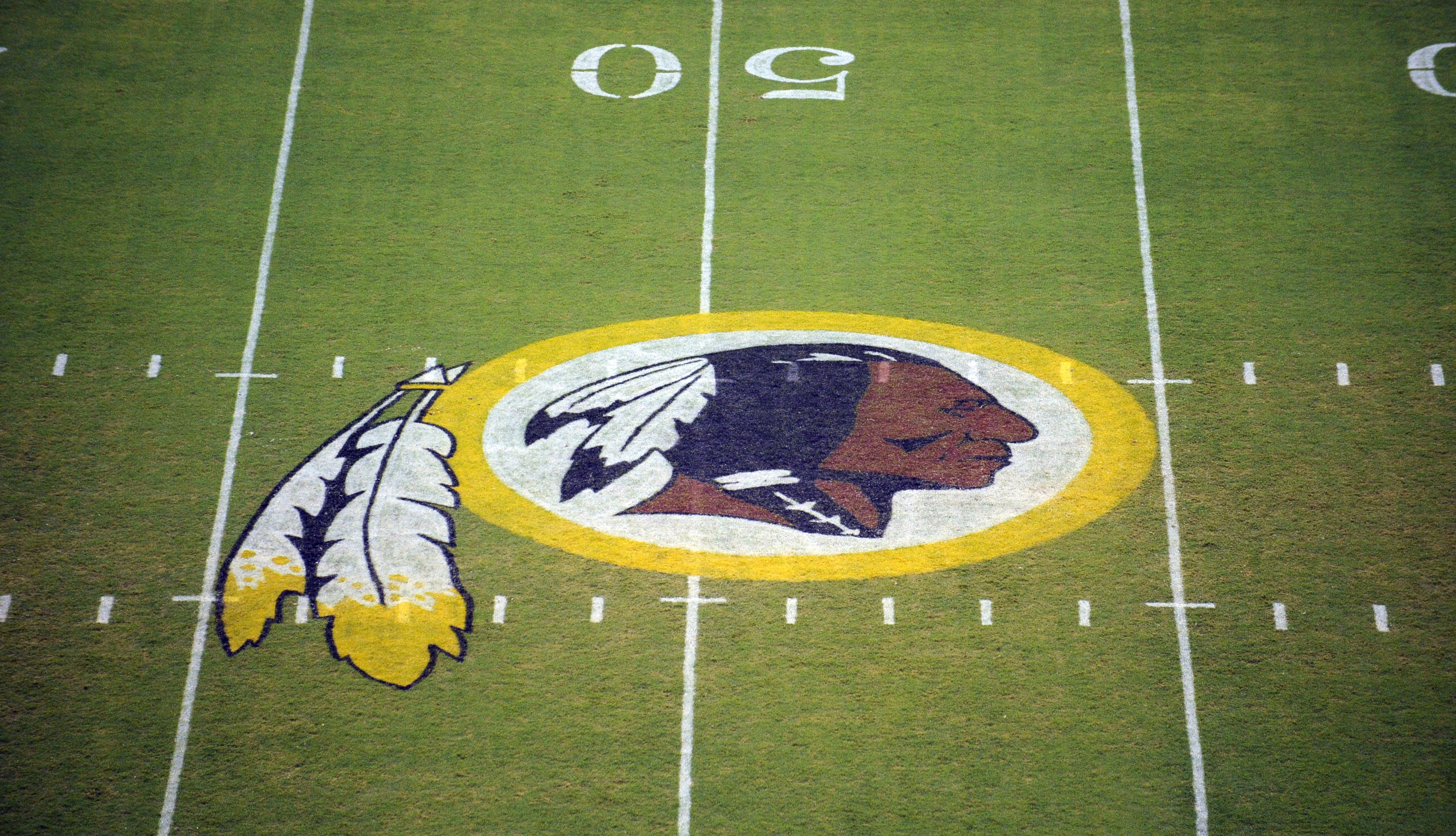 FILE - In this Aug. 28, 2009 file photo, the Washington Redskins logo is seen on the field before the start of a preseason NFL football game in Landover, Md.  A judge is hearing arguments from the Washington Redskins on June 23, 2015, that canceling the t