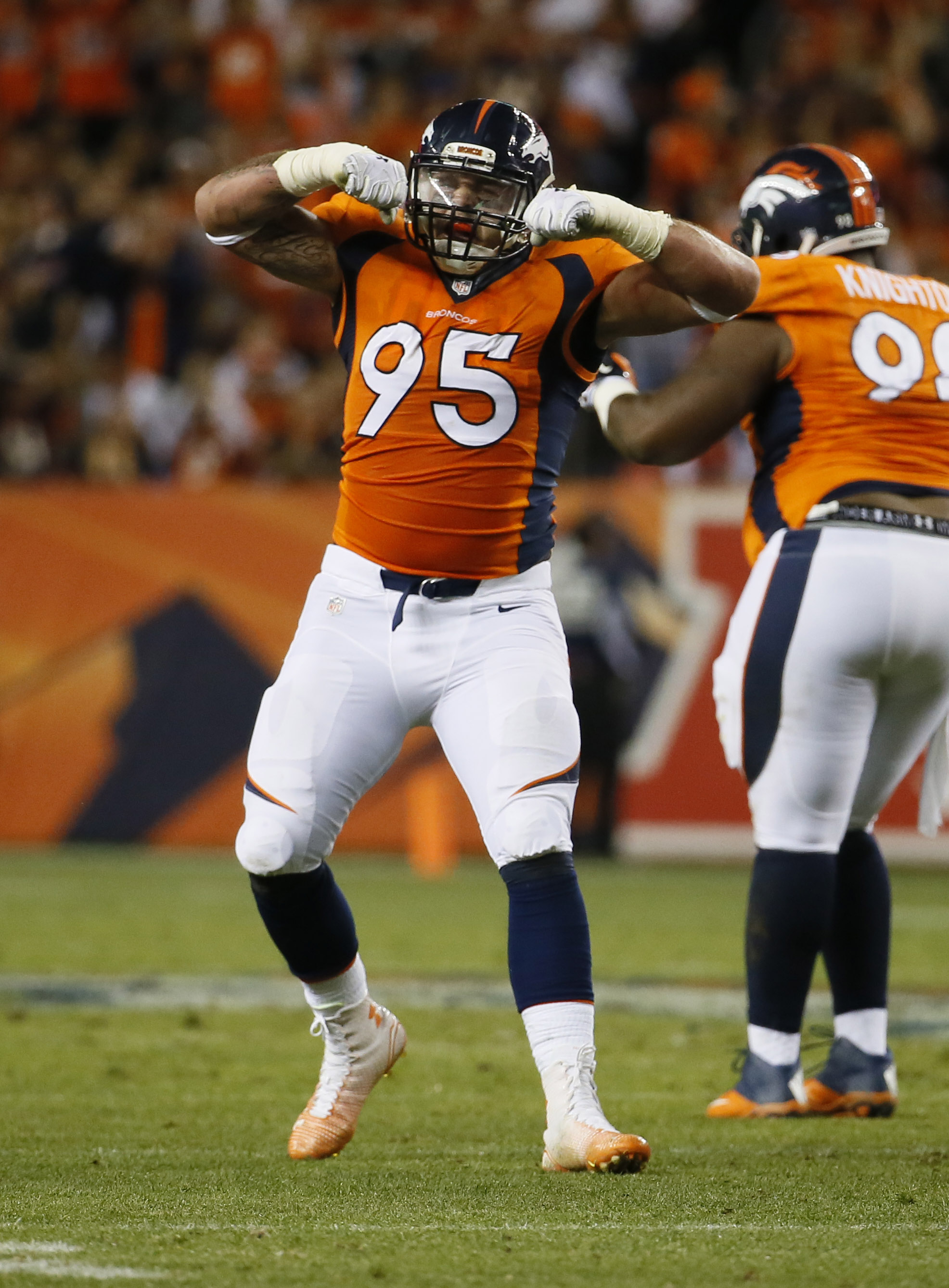 Denver Broncos defensive end Derek Wolfe (95) celebrates a stop against the San Diego Chargers during the first half of an NFL football game, Thursday, Oct. 23, 2014, in Denver. (AP Photo/Jack Dempsey)