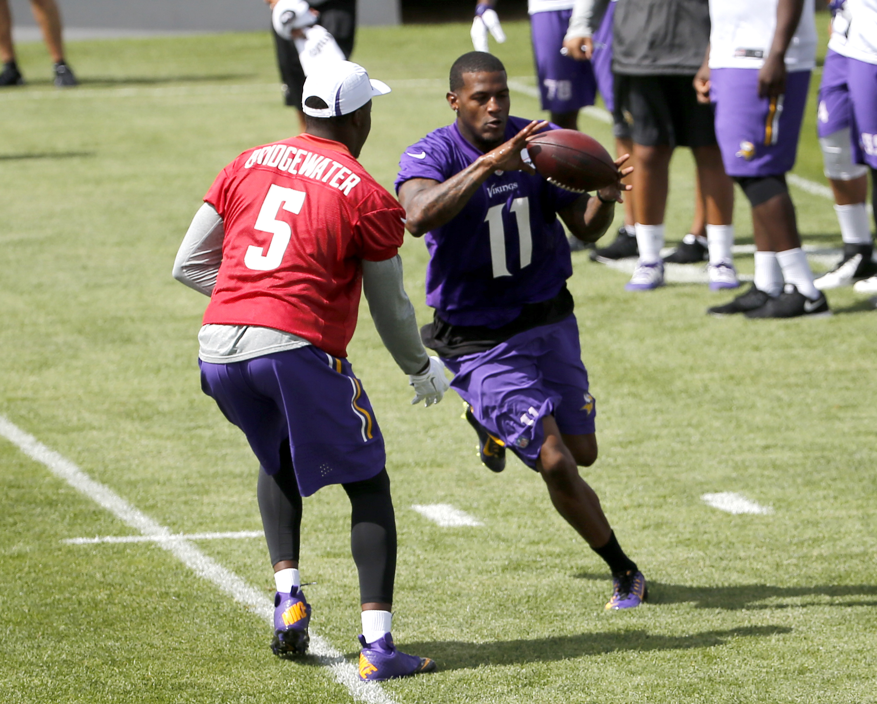 Minnesota Vikings quarterback Teddy Bridgewater (5) flips the ball to wide receiver Mike Wallace (11) on an end-around during practice at an NFL football training camp on the campus of Minnesota State University, Sunday, July 26, 2015, in Mankato, Minn. (