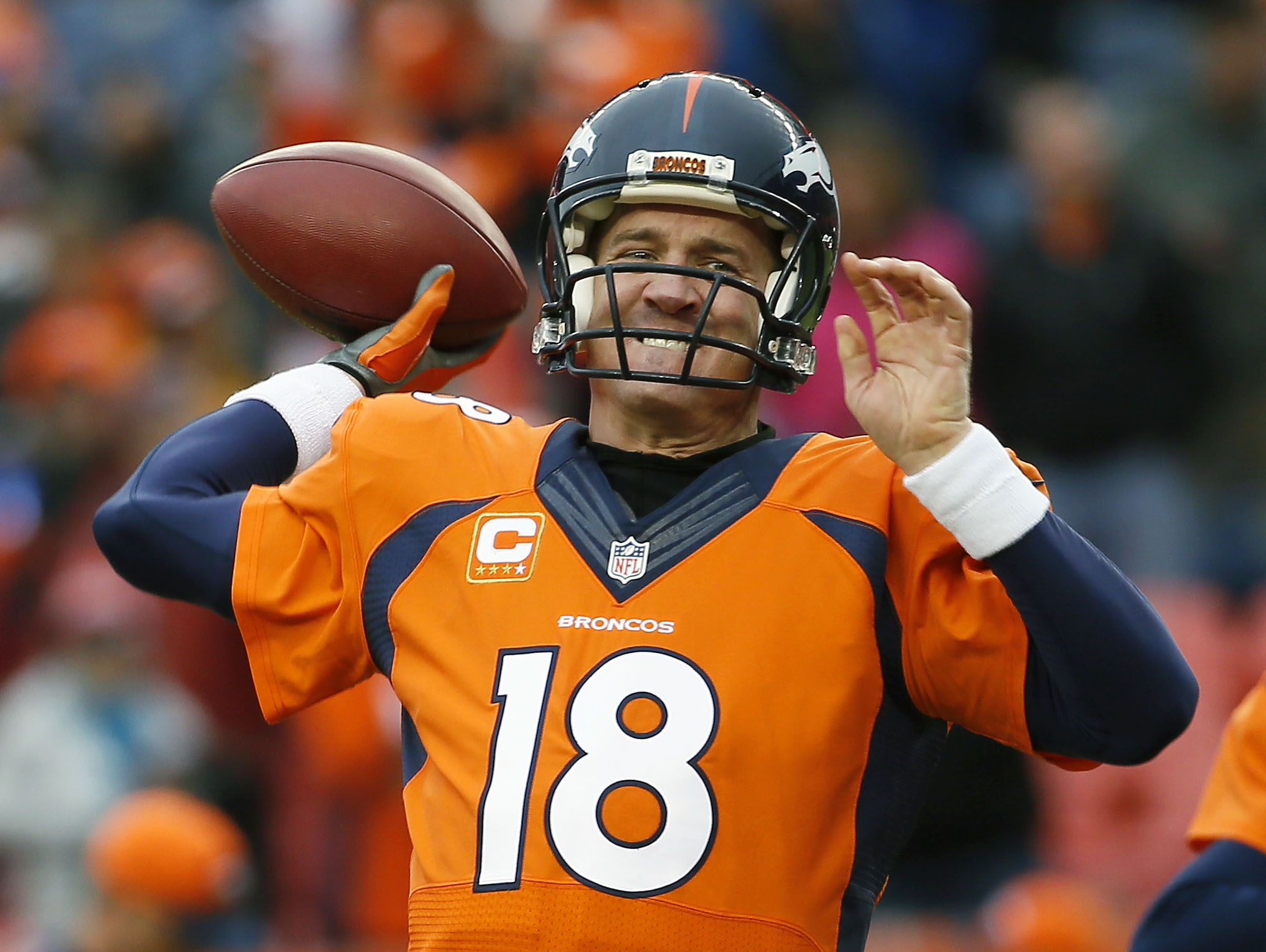 FILE - In this Sunday, Jan. 11, 2015, file photo, Denver Broncos quarterback Peyton Manning (18) warms up prior to an NFL divisional playoff football game against the Indianapolis Colts in Denver. Manning can earn back every penny of the $4 million pay cu