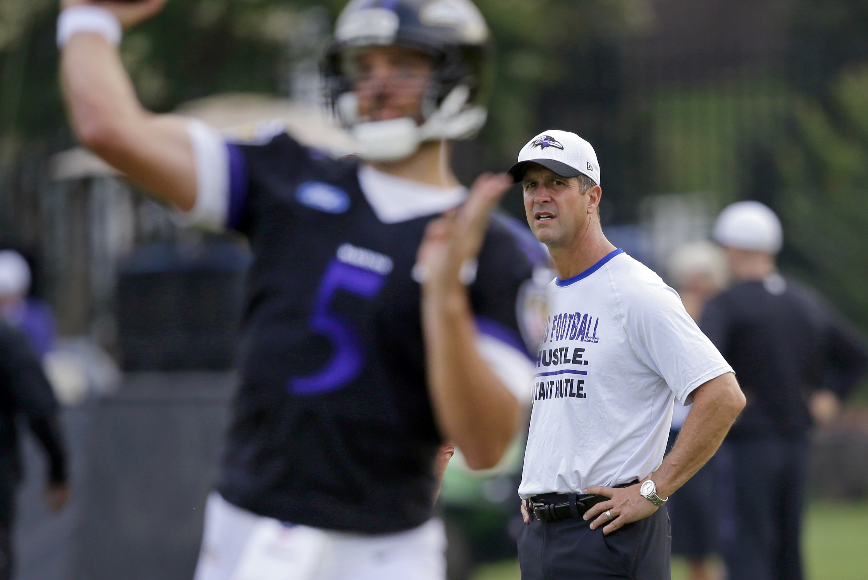 Baltimore Ravens head coach John Harbaugh, right, watches quarterback Joe Flacco throw a pass at the team's first day of NFL football training camp, Thursday, July 30, 2015, in Owings Mills, Md. (AP Photo/Patrick Semansky)